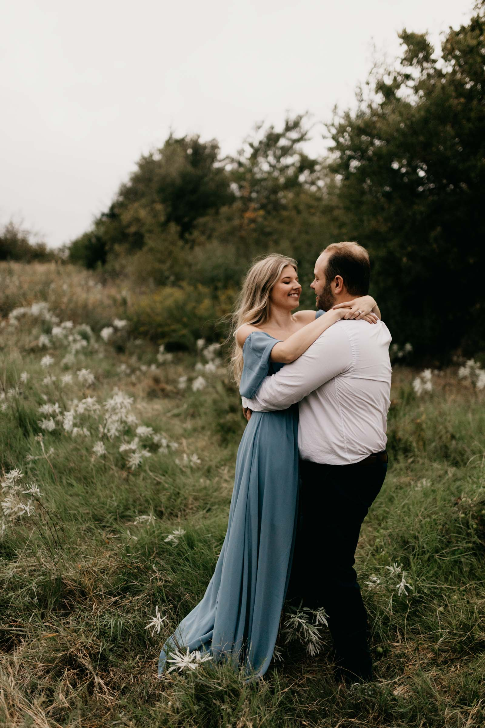 girl wearing blue dress and boy wearing casual suit in a green pasture for engagement photos