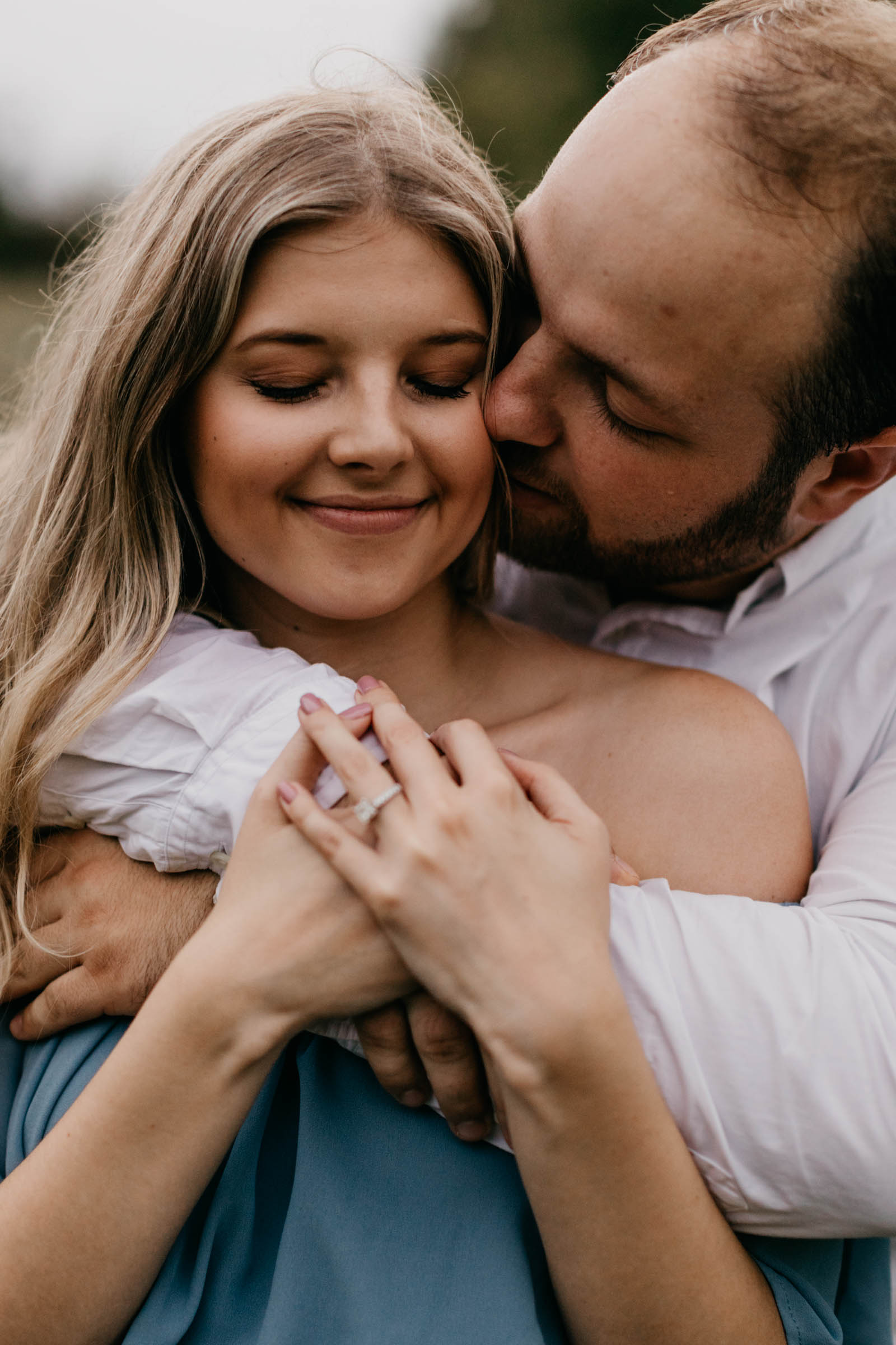 boy hugging fiancé over the shoulders during their engagement session in Fort Worth