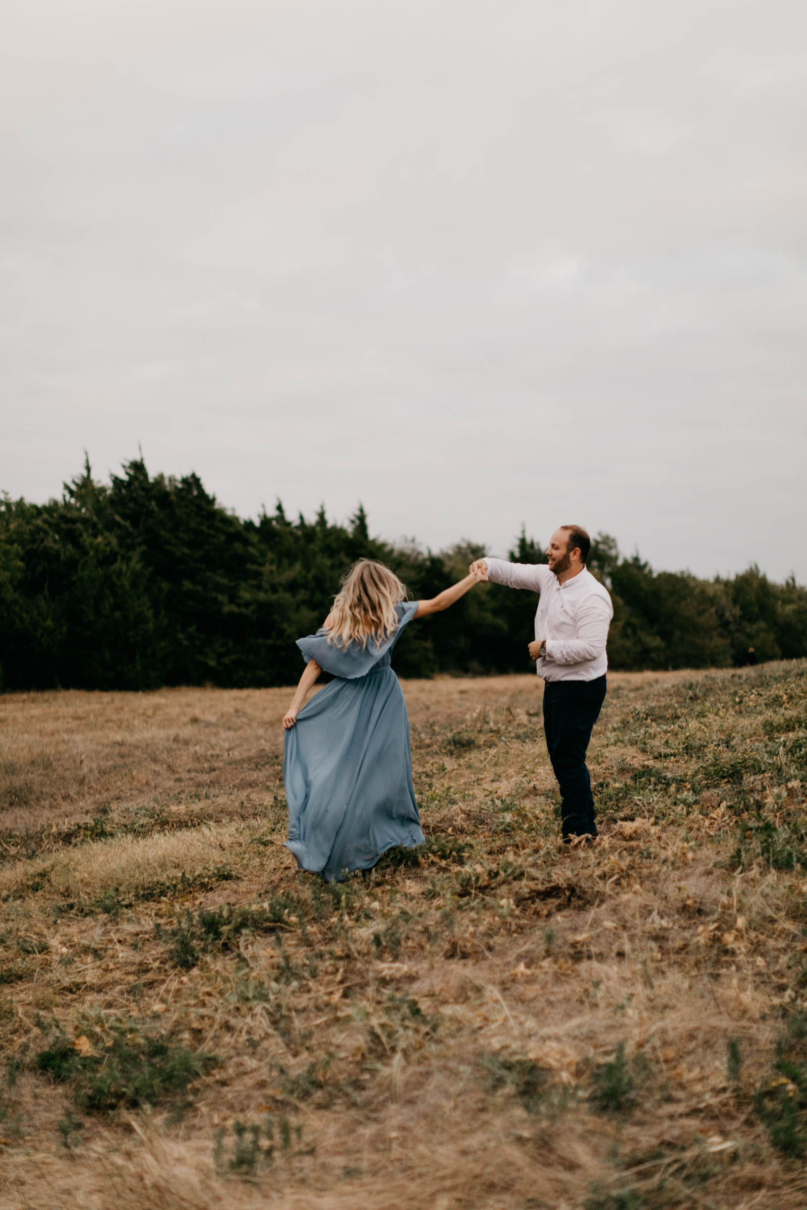 engaged couple dancing on top of a hill wearing formal clothes for their engagement session in north texas