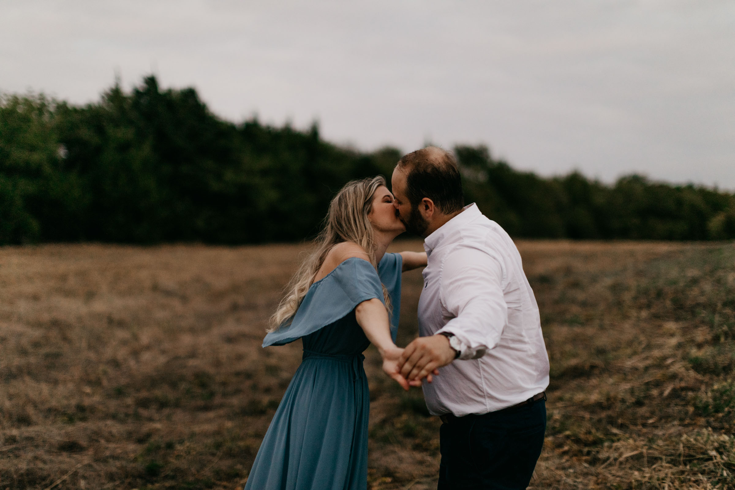 boy and girl kissing and being romantic for their engagement photos during fall in north texas