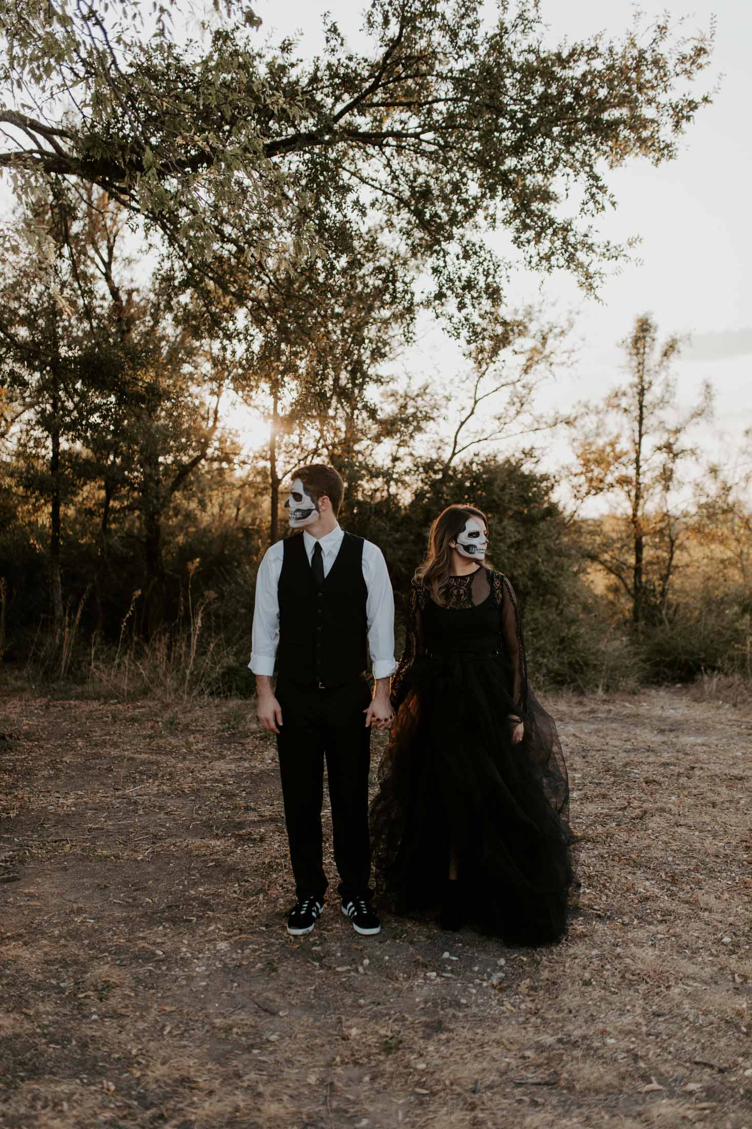 couple dressed in halloween costume takes spooky photo in a park