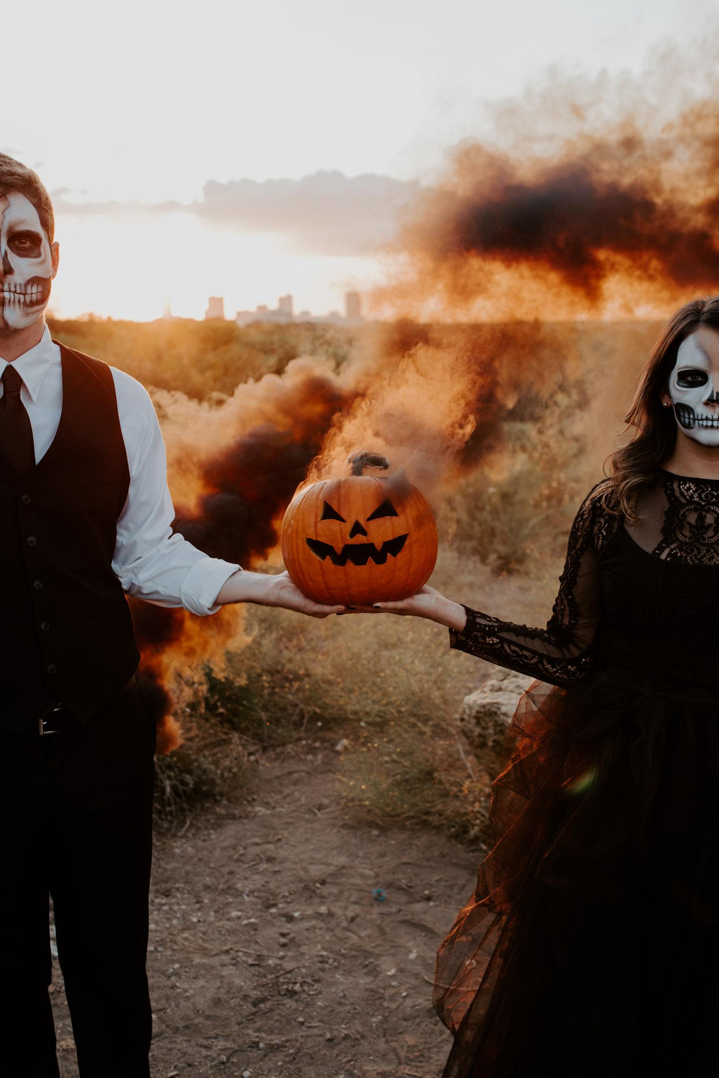 couple wearing skeleton makeup holding a jack-o-lantern with a smoke bomb inside