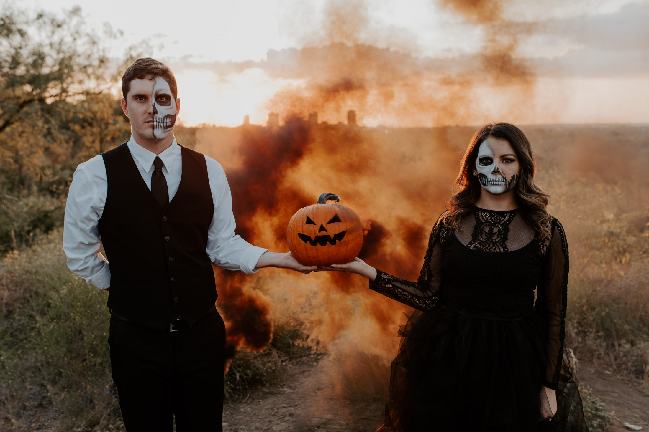 couple standing side by side holding a pumpkin with a black smoke bomb at sunset