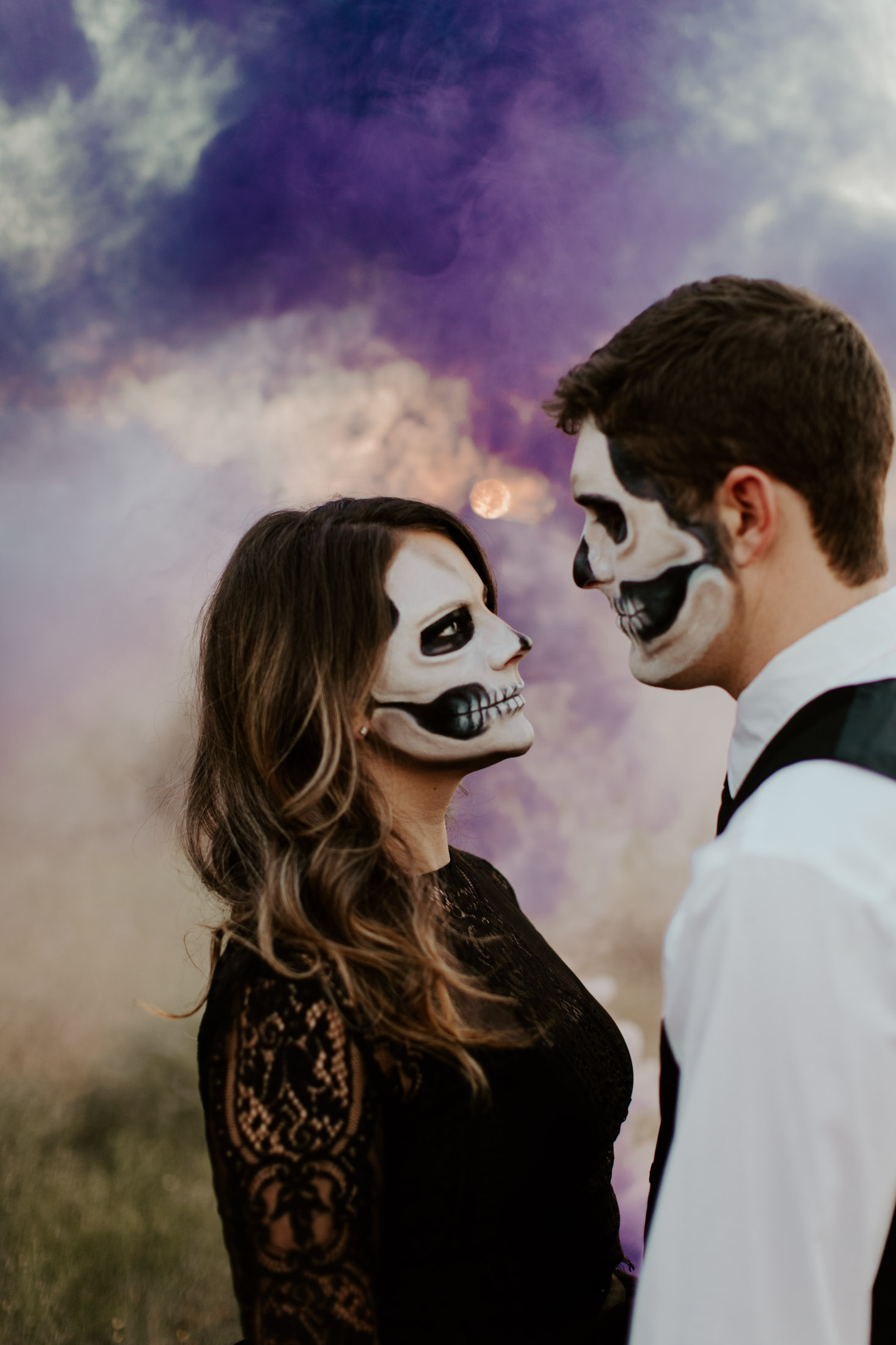 spooky photo of couple with purple smoke bomb in the background