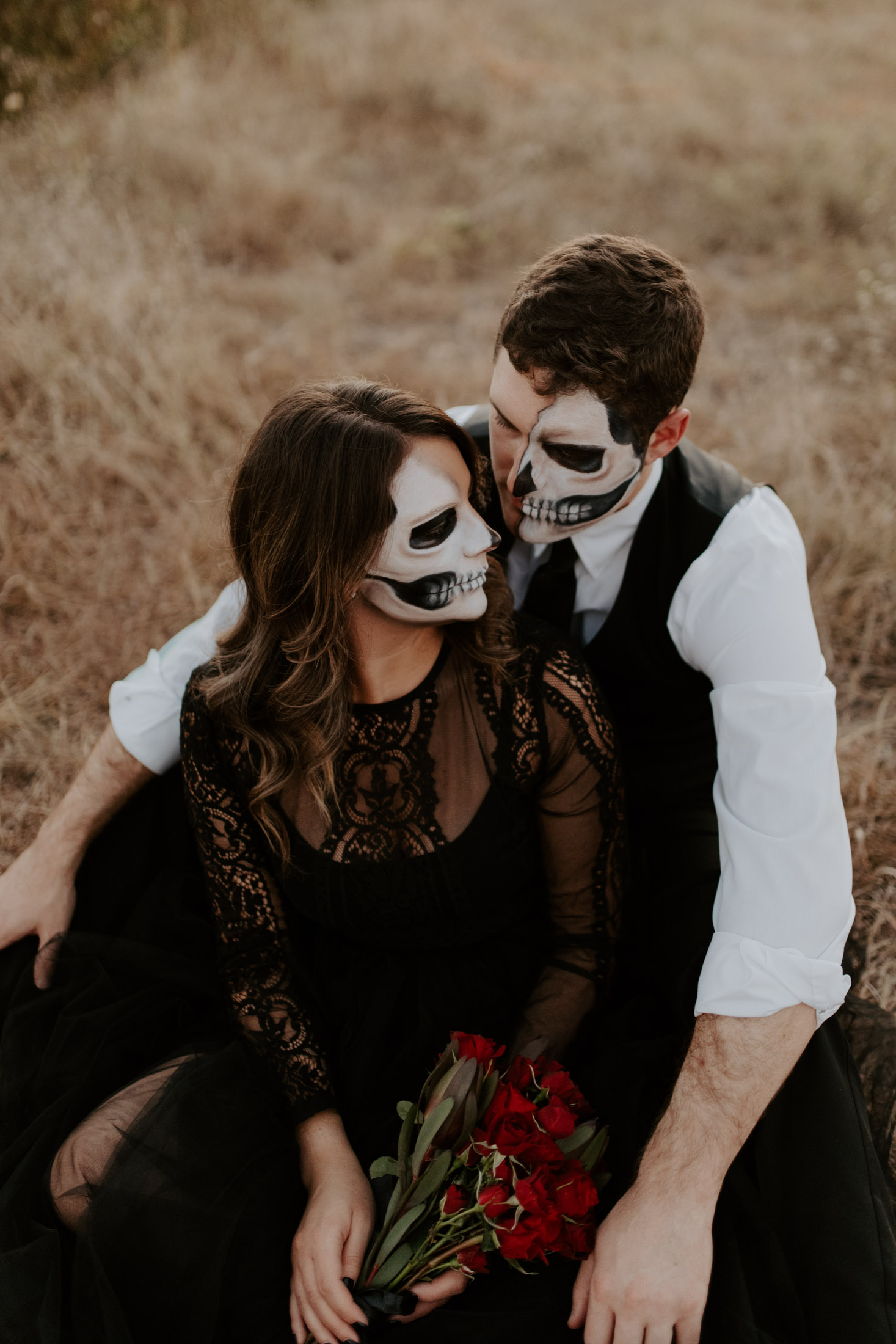 halloween inspired couple sitting on the ground for a photo shoot