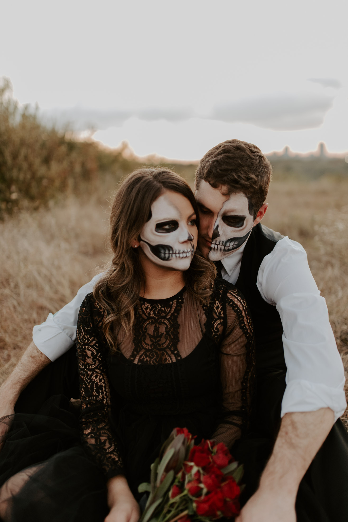 coy and girl with skeleton makeup on sitting close during a spooky photo session