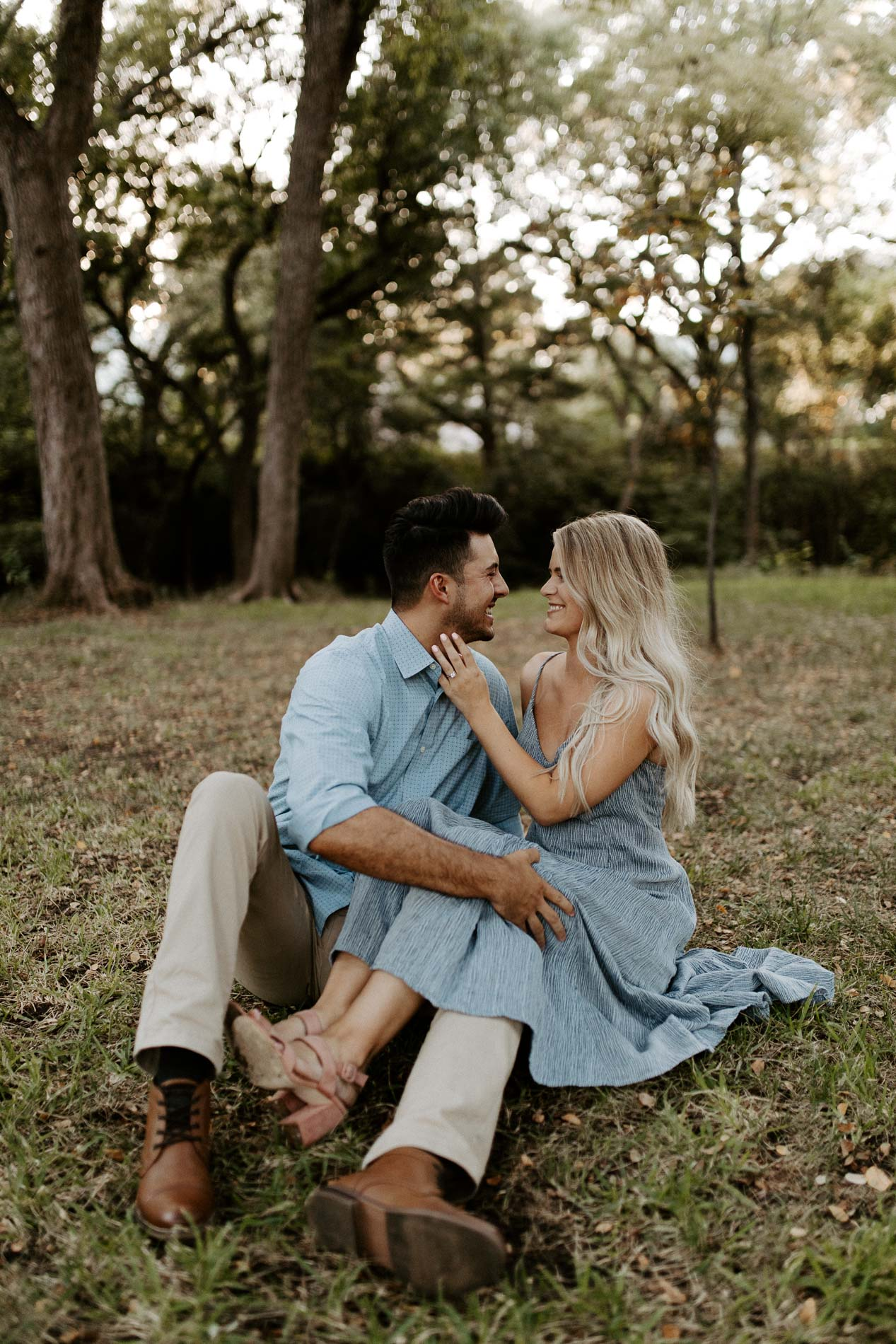 Engaged couple sitting in grass in a beautiful location for their engagement photos