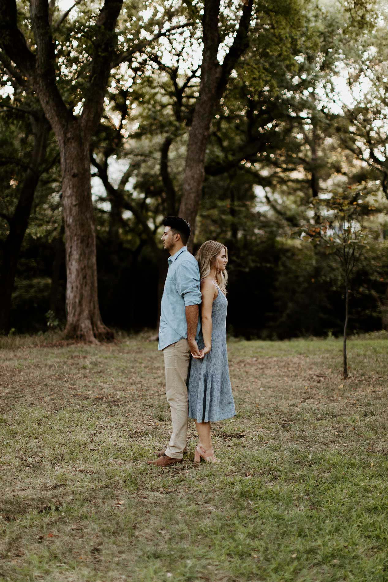 Couple standing back to back in a natural area in Dallas Texas for engagement photos