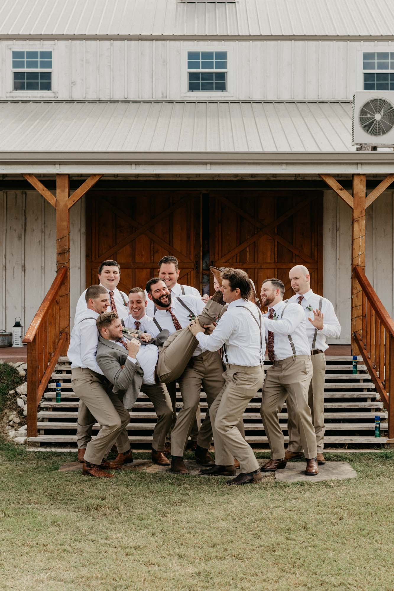 Groom being thrown in air by groomsmen at a fun wedding