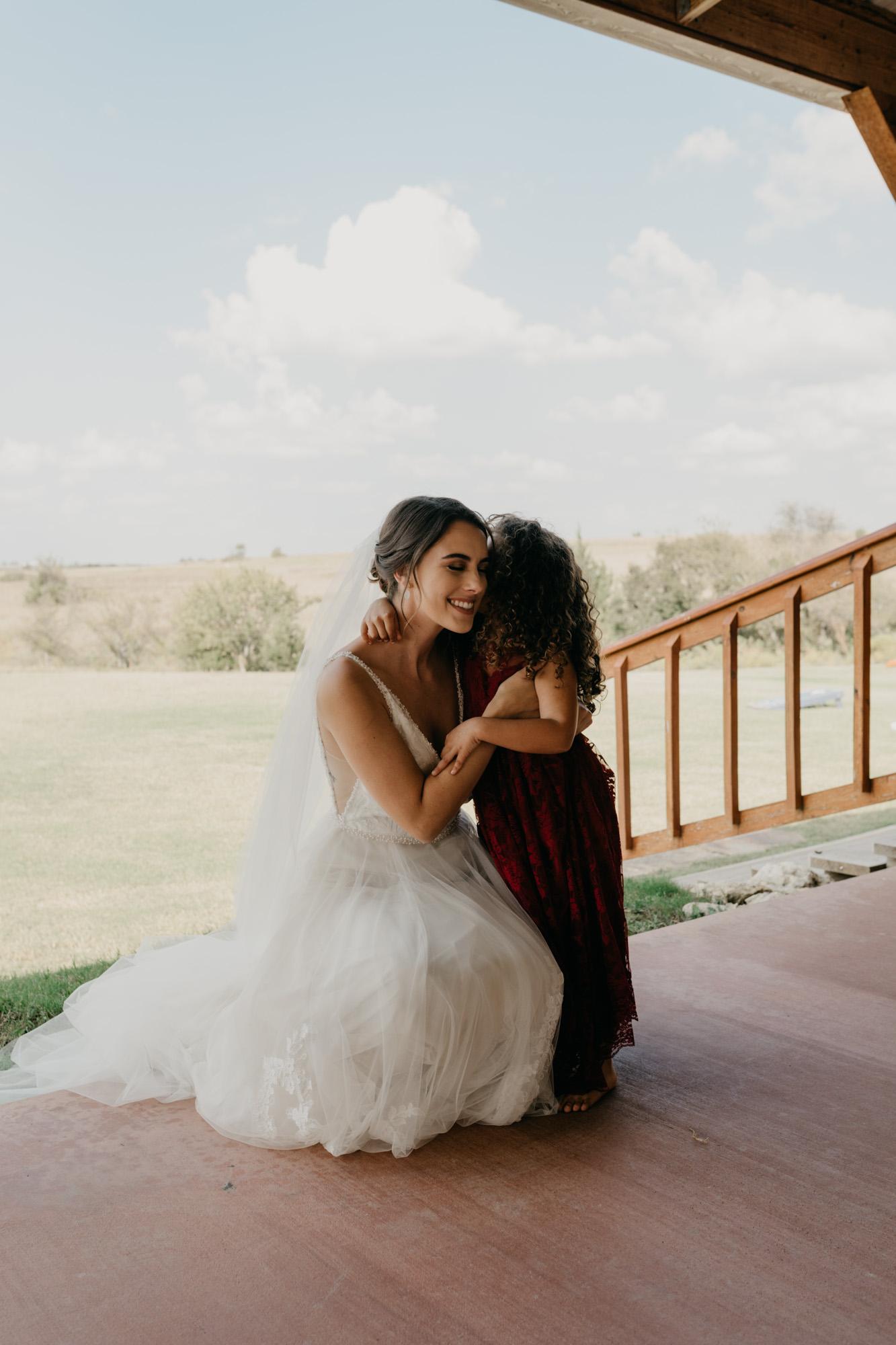 Bride hugging flower girl on porch of wedding venue