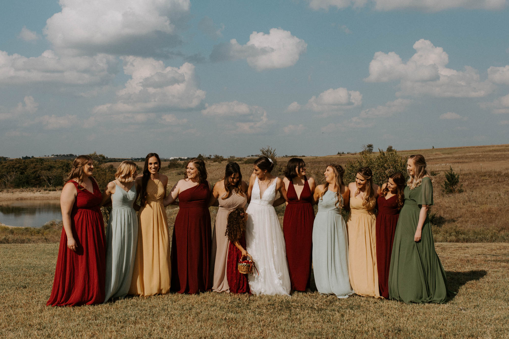 bridal party taking candid photos in field in north texas