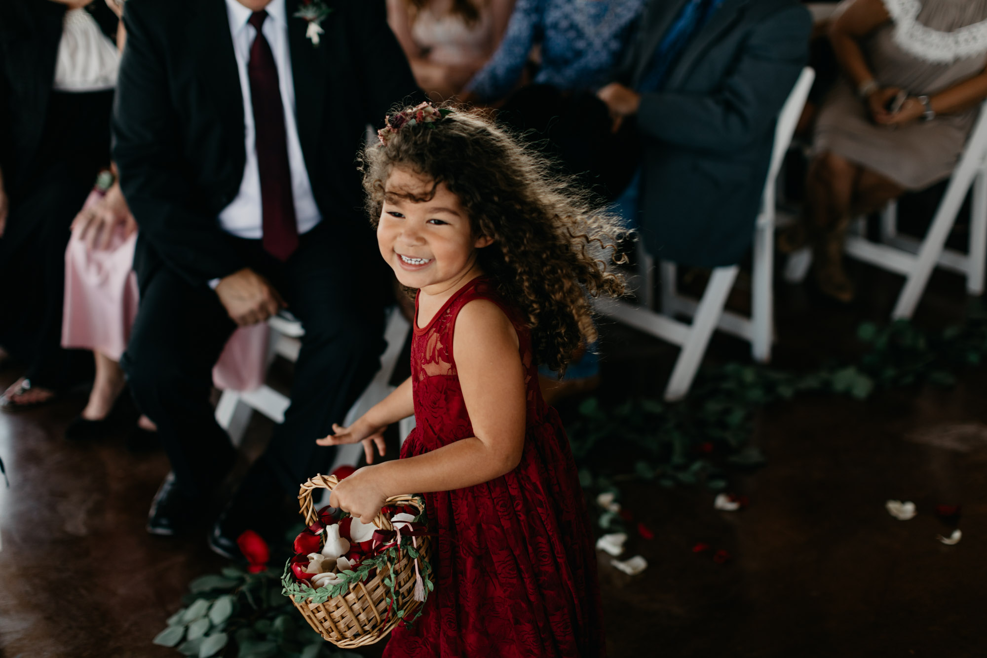 flower girl happily walking down the aisle