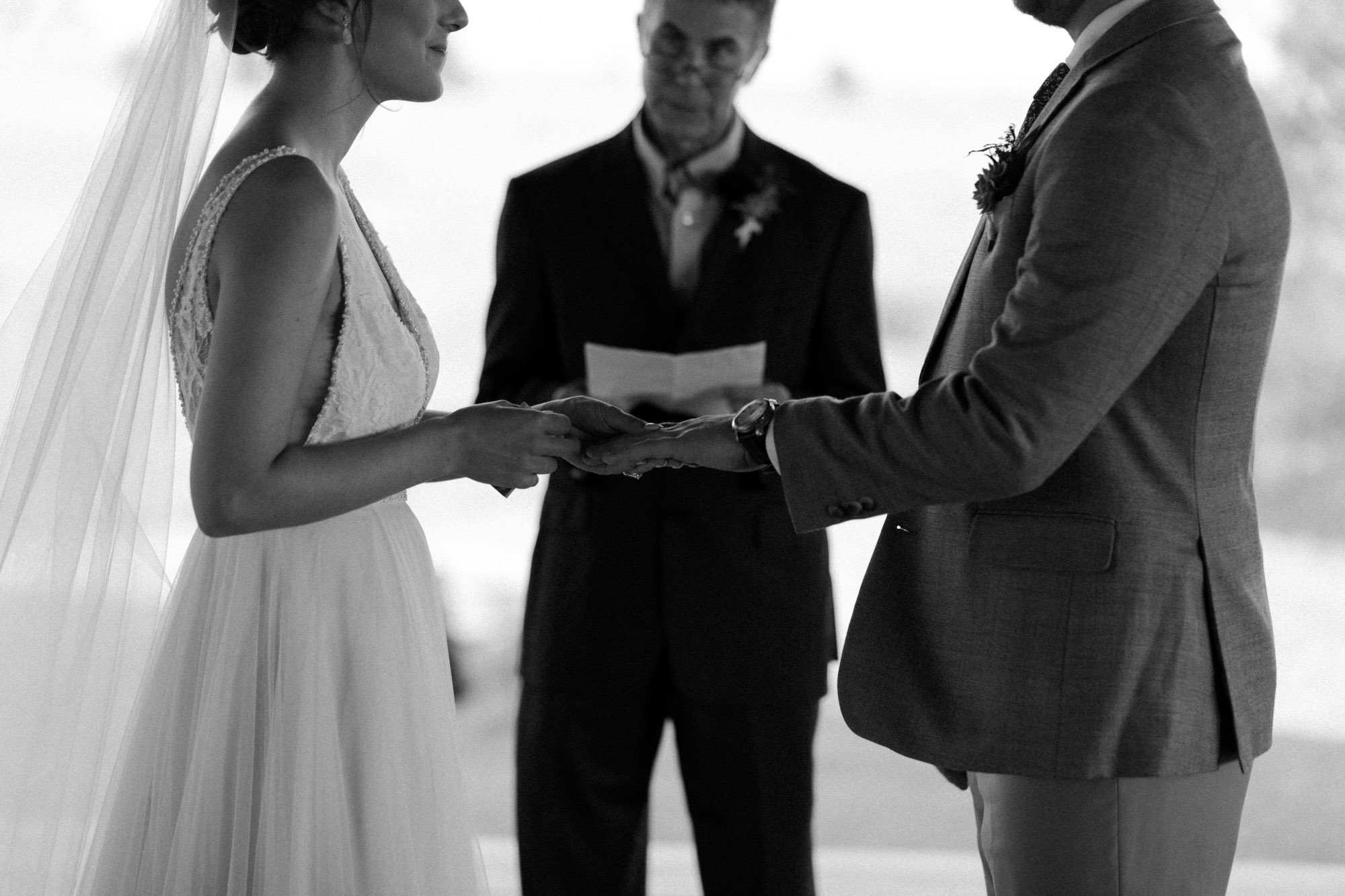 Black and white close up photo of bride and groom exchanging rings