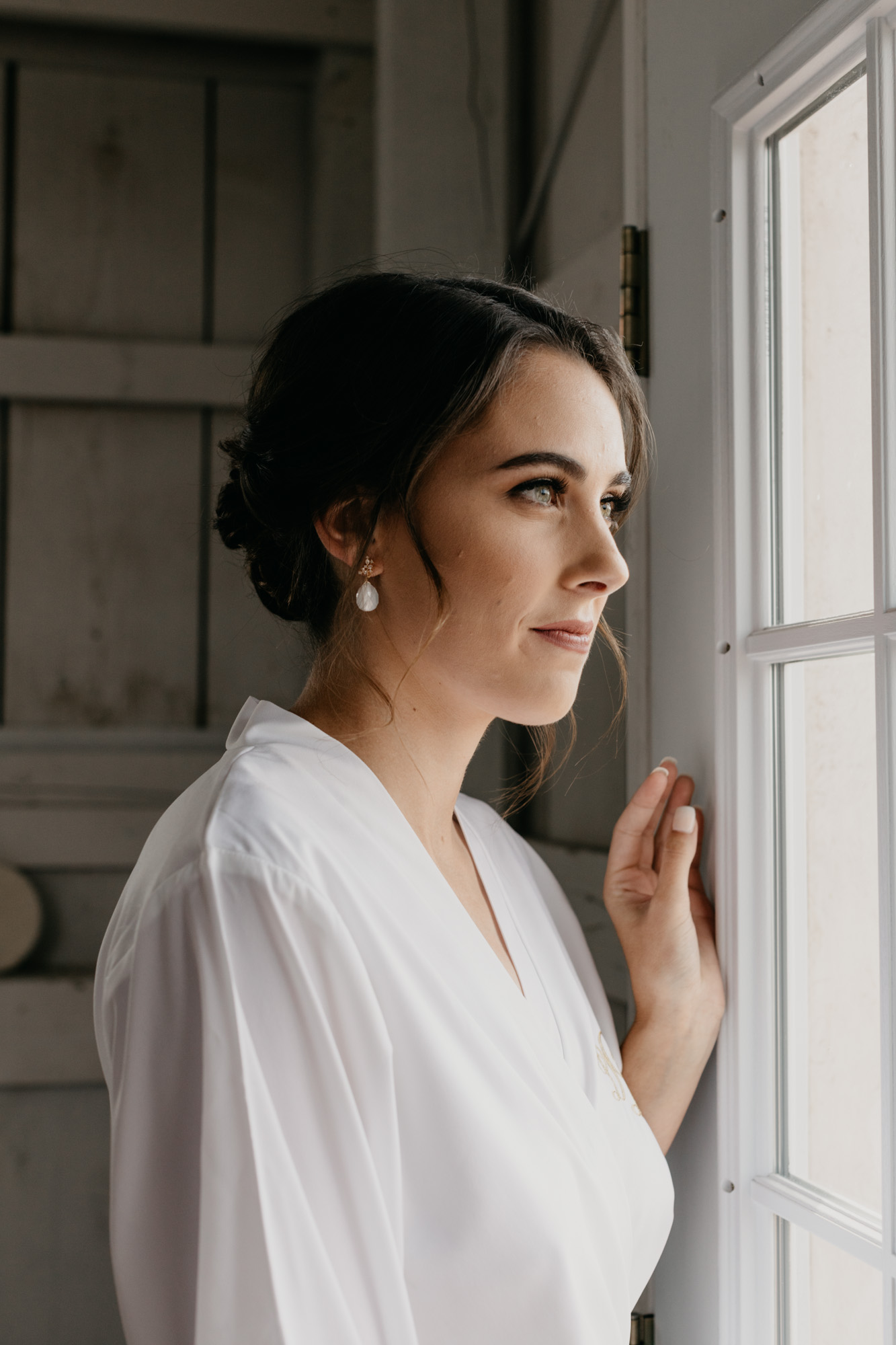 Bride looking out window for photographer on her north Texas wedding day