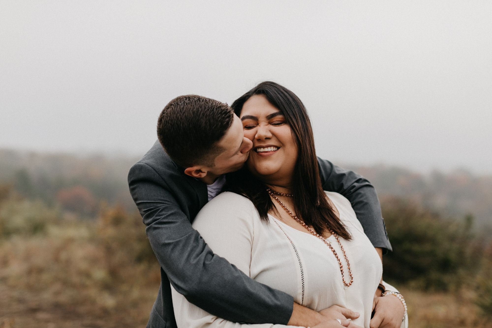 boy hugging girl from behind at anniversary session