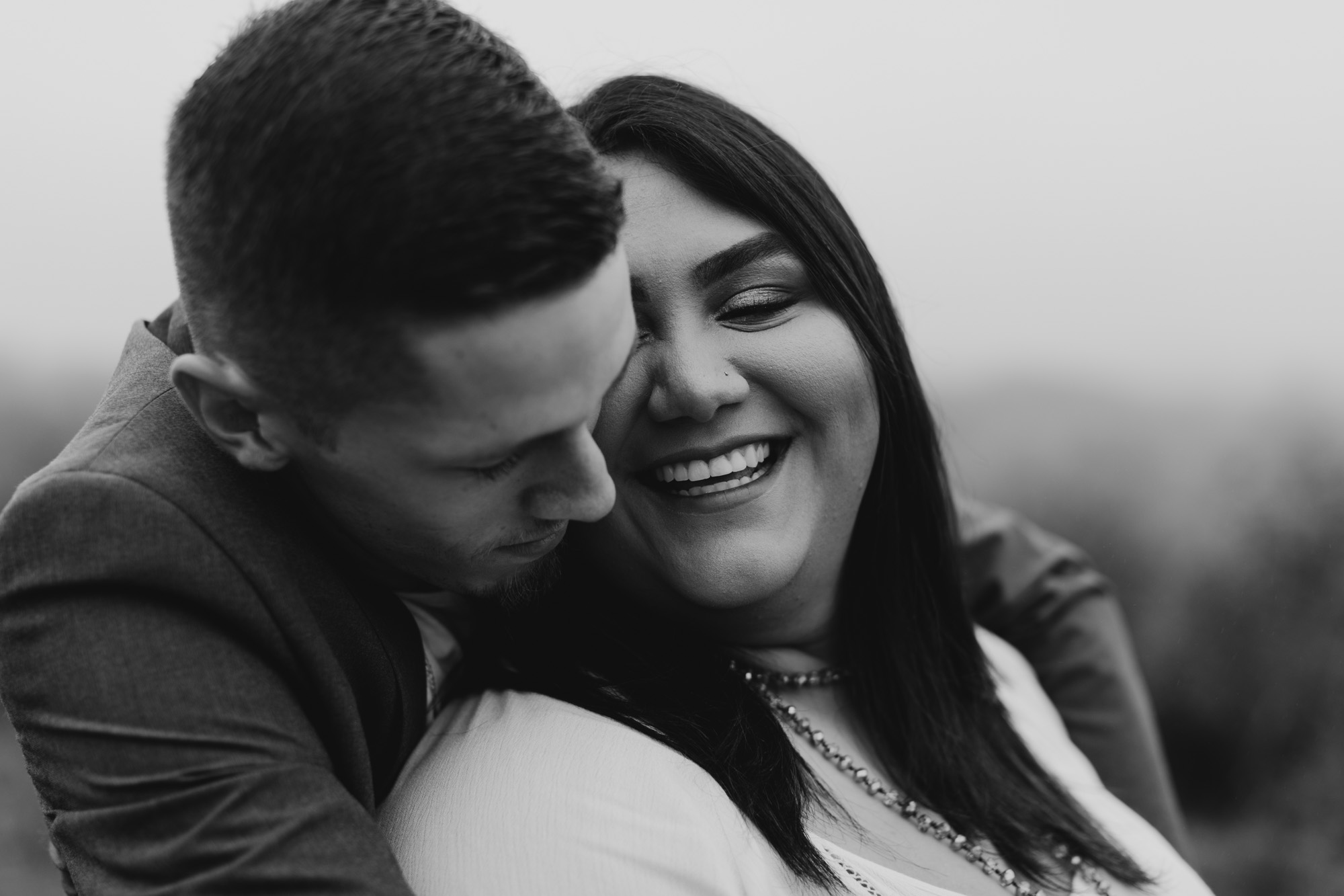 black and white anniversary photo of snuggly couple
