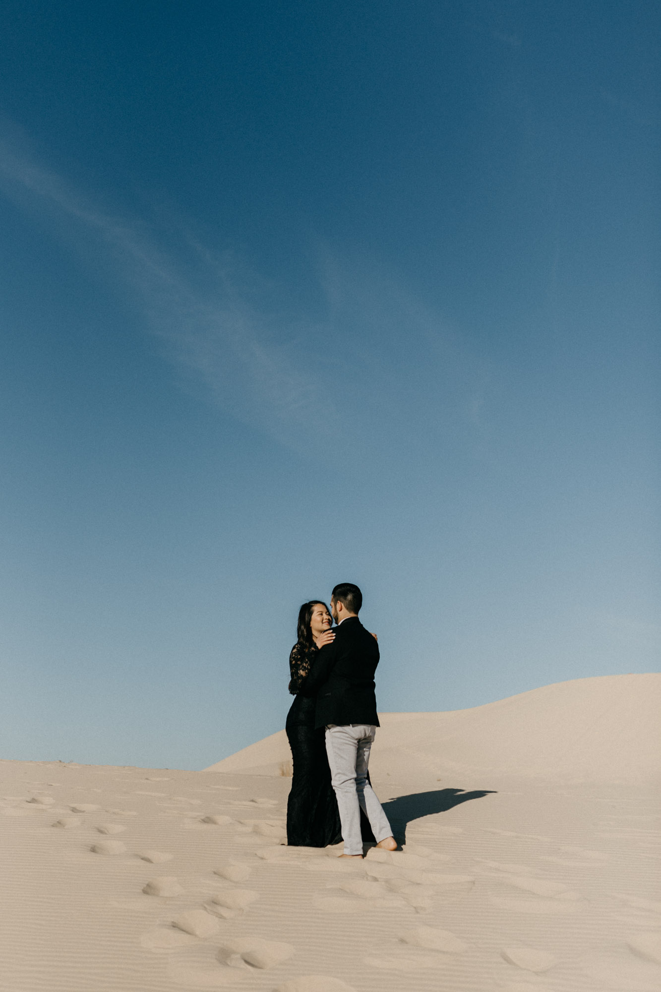 Couple looking at each other during their sand hills engagement session in west Texas - ideas for couples photography