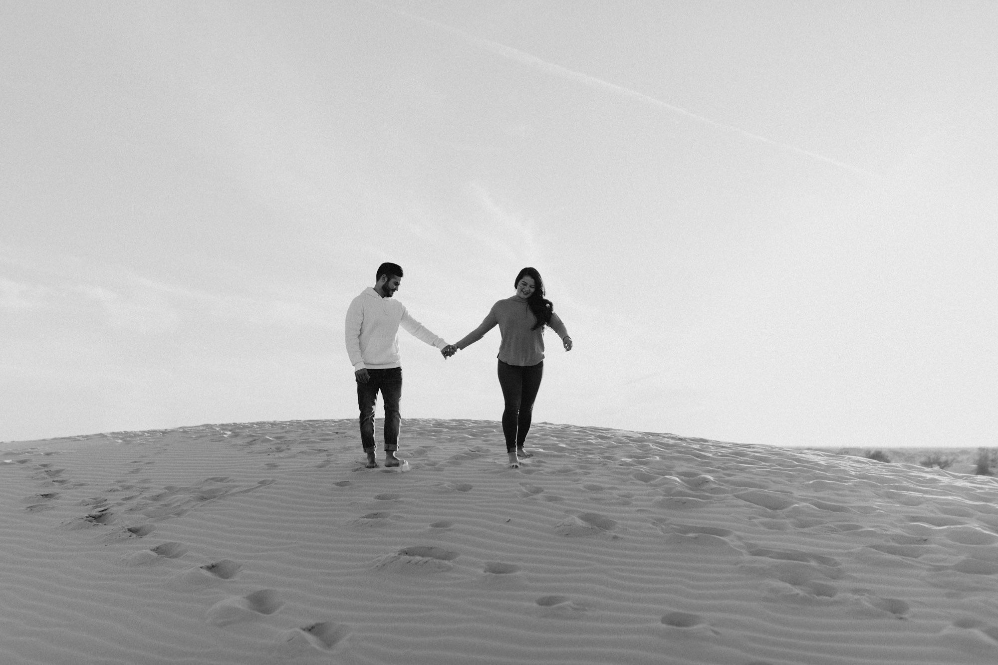 Black and white photo of a couple strolling at the sand hills in west texas