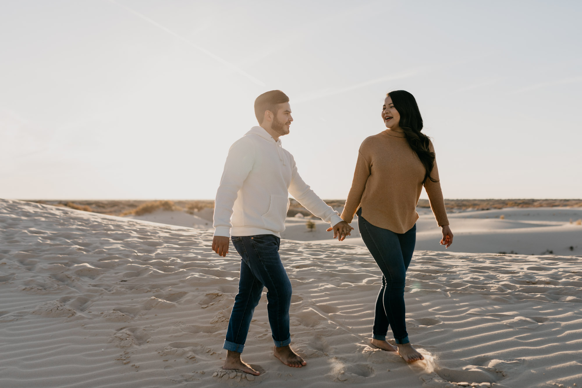 Adorable couple walking in the sand hills in west texas