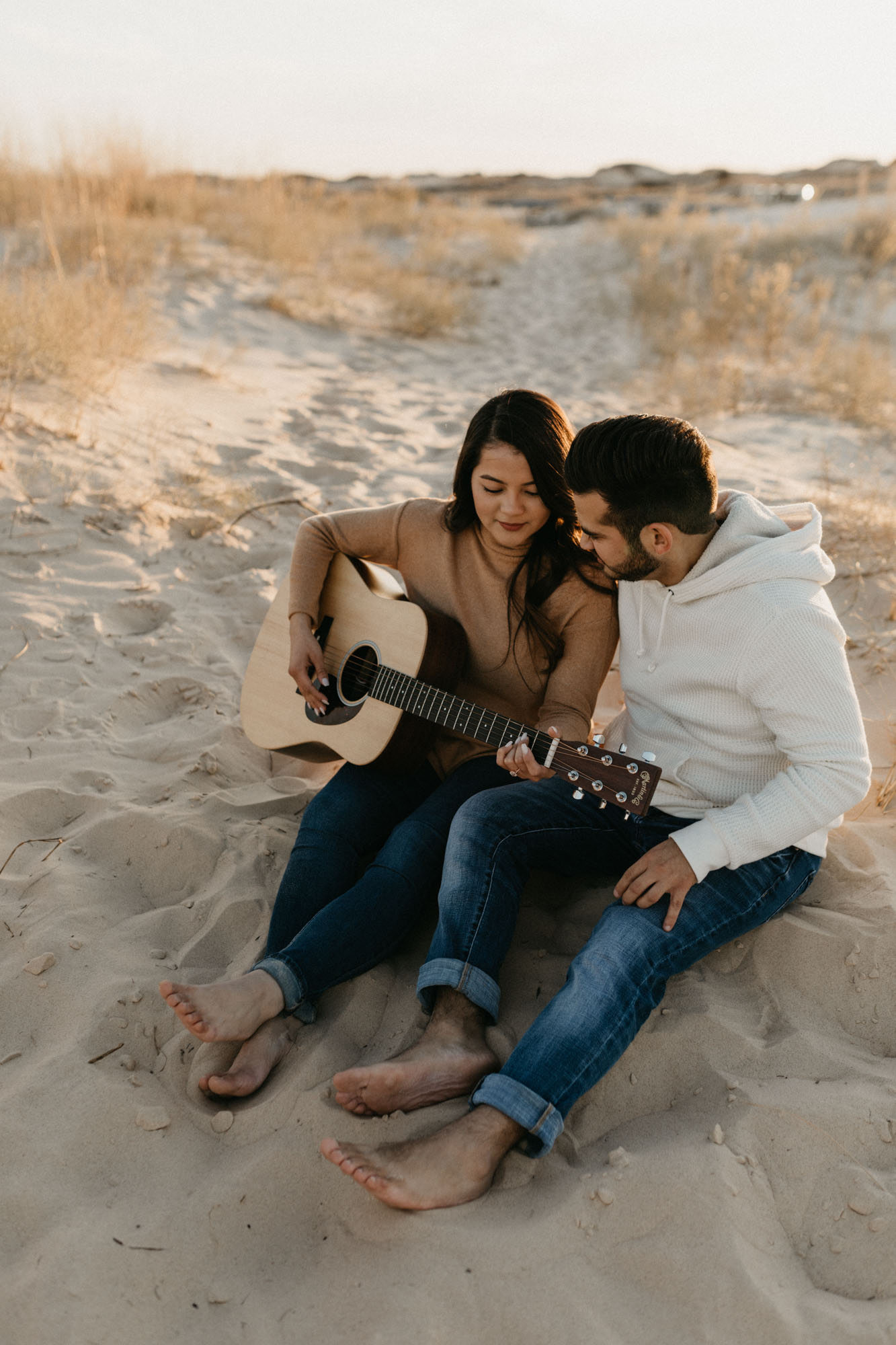 Golden hour couple playing guitar during an engagement session