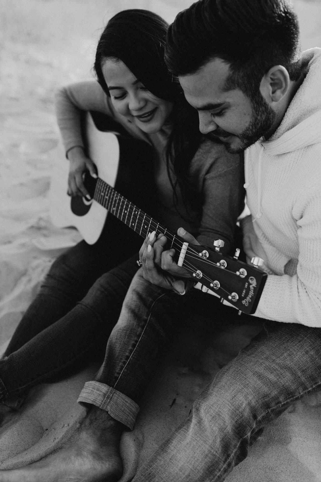 Natural candid photos of couple playing their guitar during an engagement session at sand hills