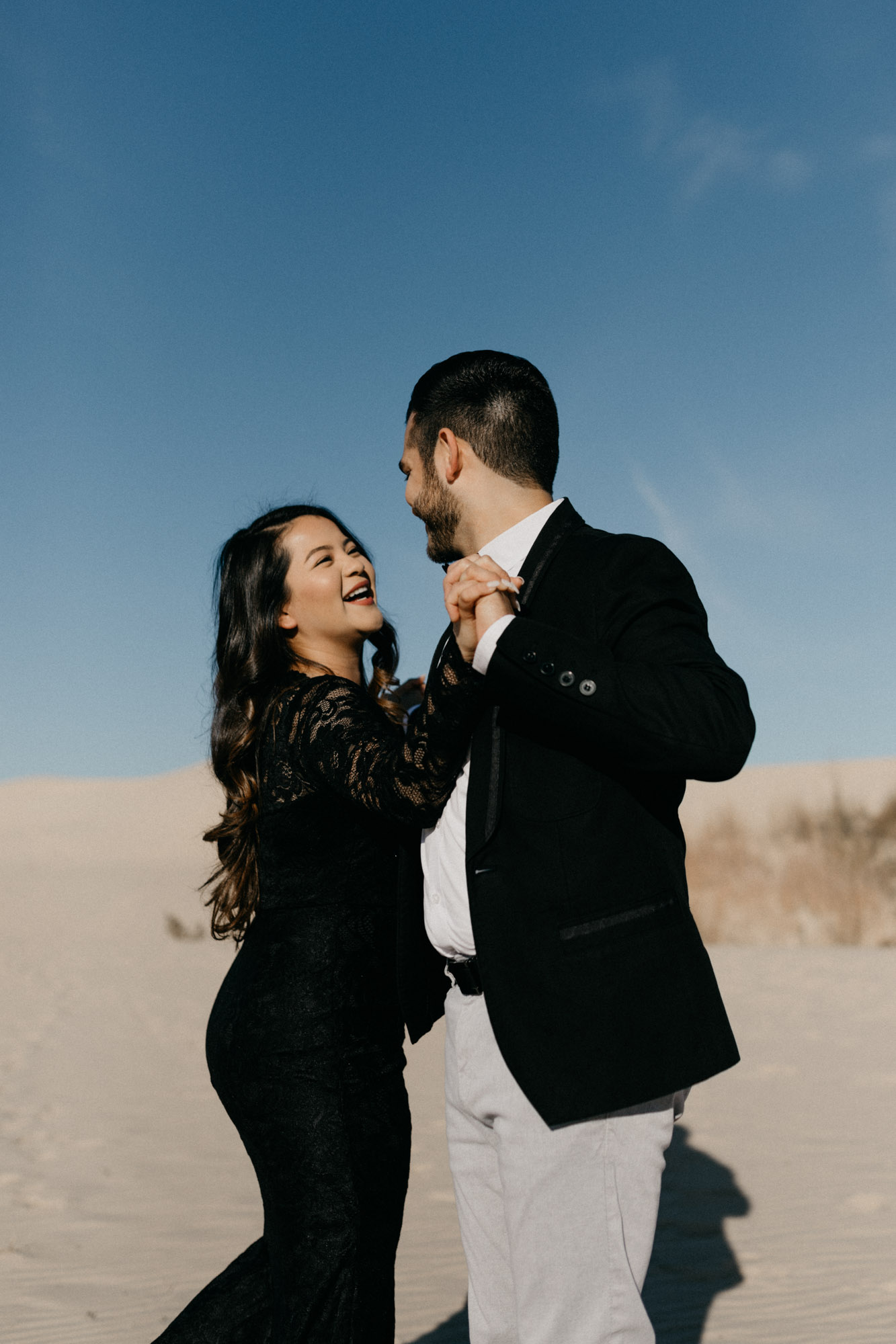 Engaged couple being playful at sand hills during their engagement session