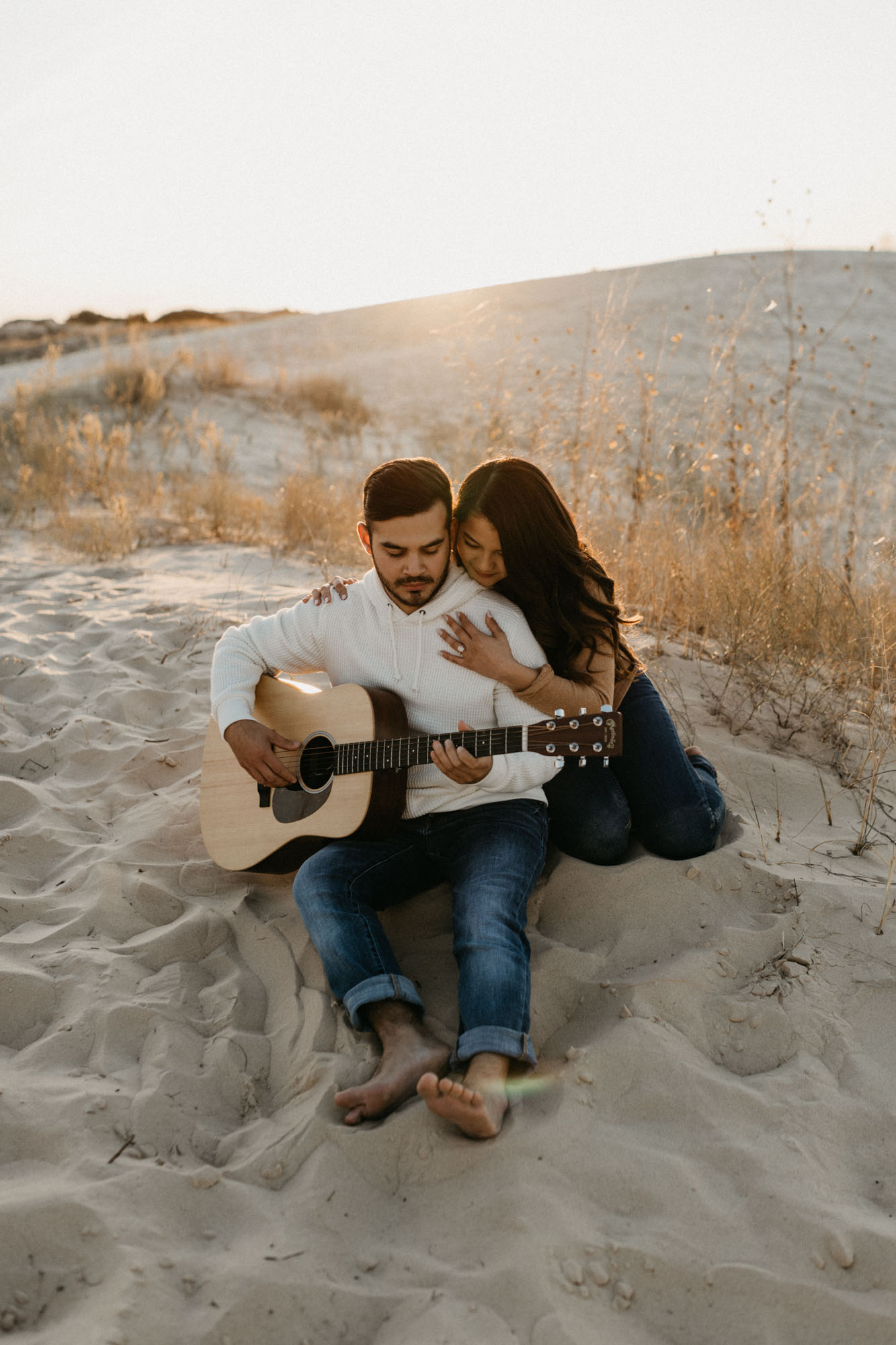 Romantic candid photo of couple playing guitar in the desert