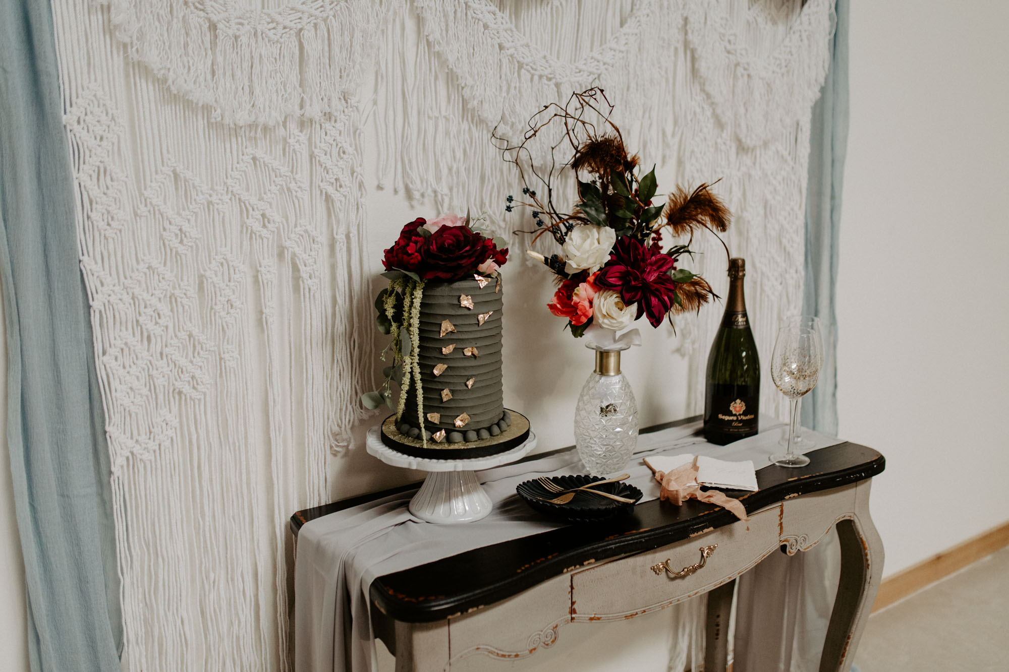 moody cake table with macrame backdrop
