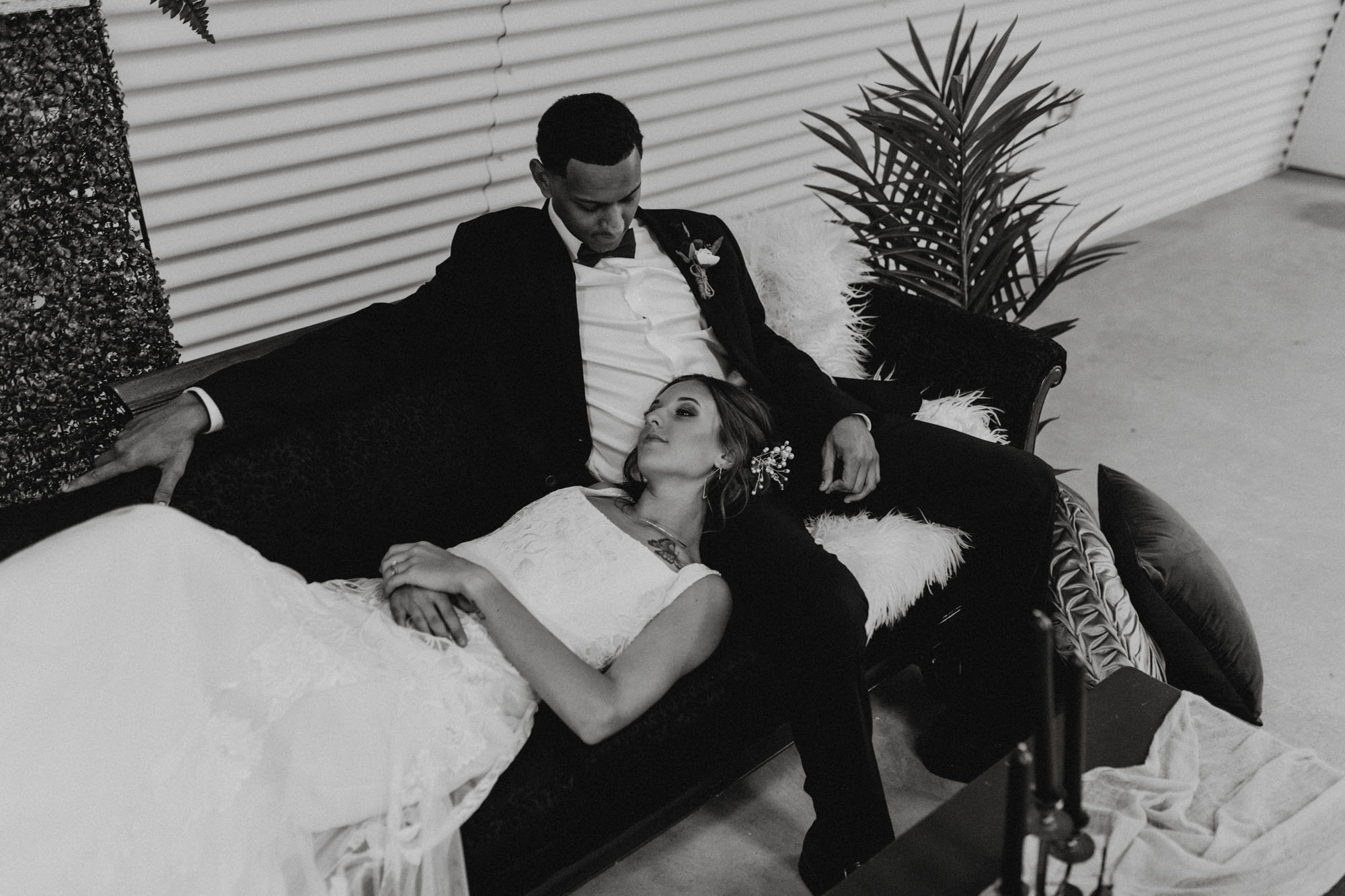 black and white photo of bride laying in grooms lap