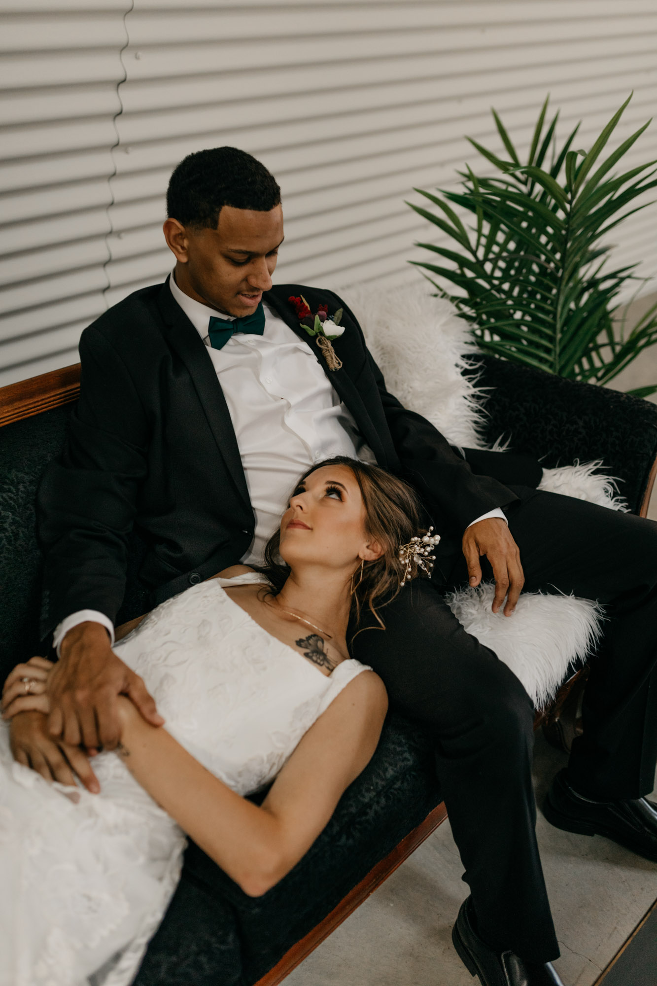 moody photo of bride laying in grooms lap