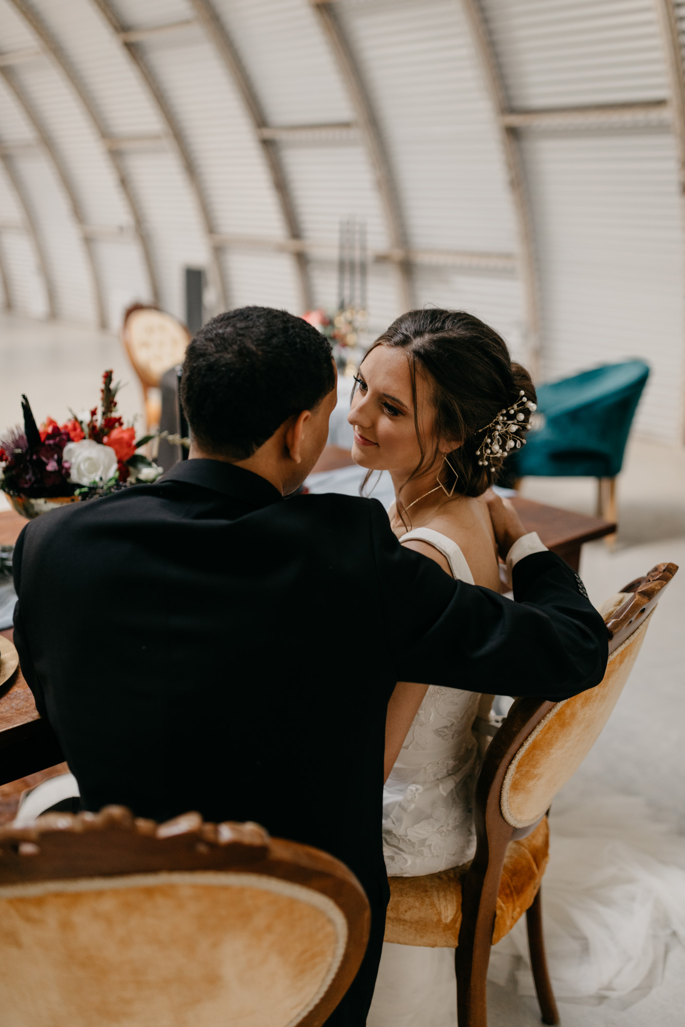 bride and groom sitting at table during moody styled shoot in Fort Worth Texas