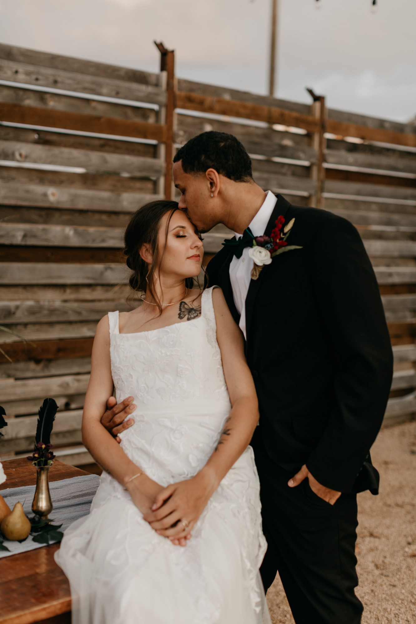groom kissing bride on the head during moody styled shoot