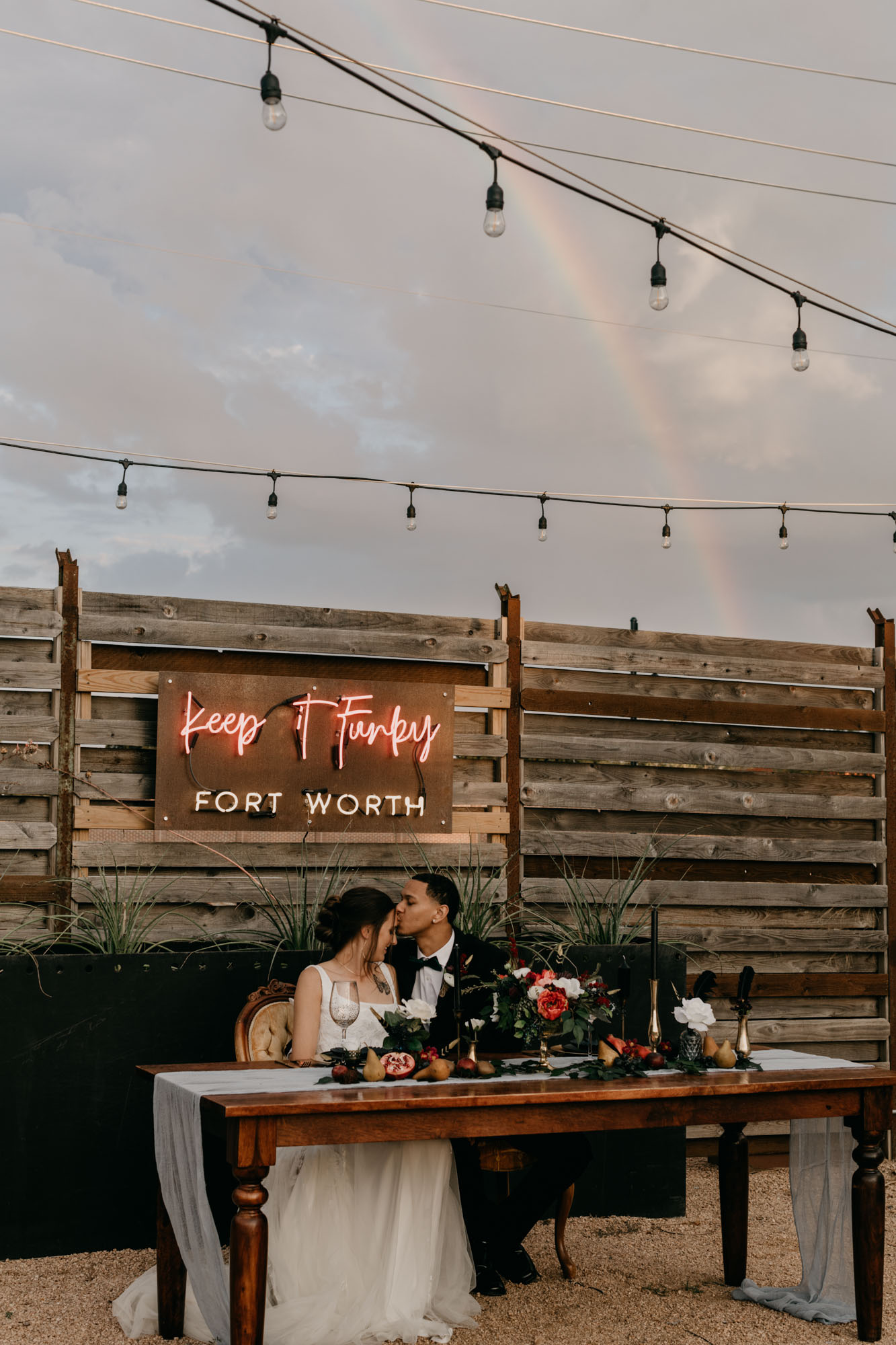 bride and groom kissing in front of red neon wedding sign with rainbow in background