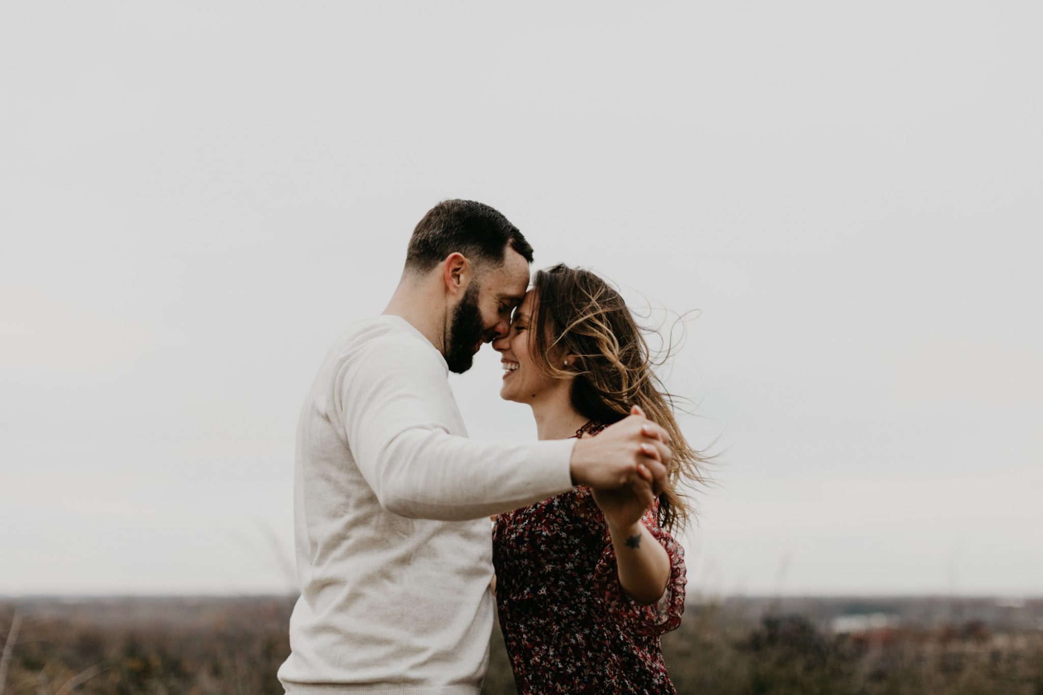 Messy wind blown hair during winter engagement session in Fort Worth