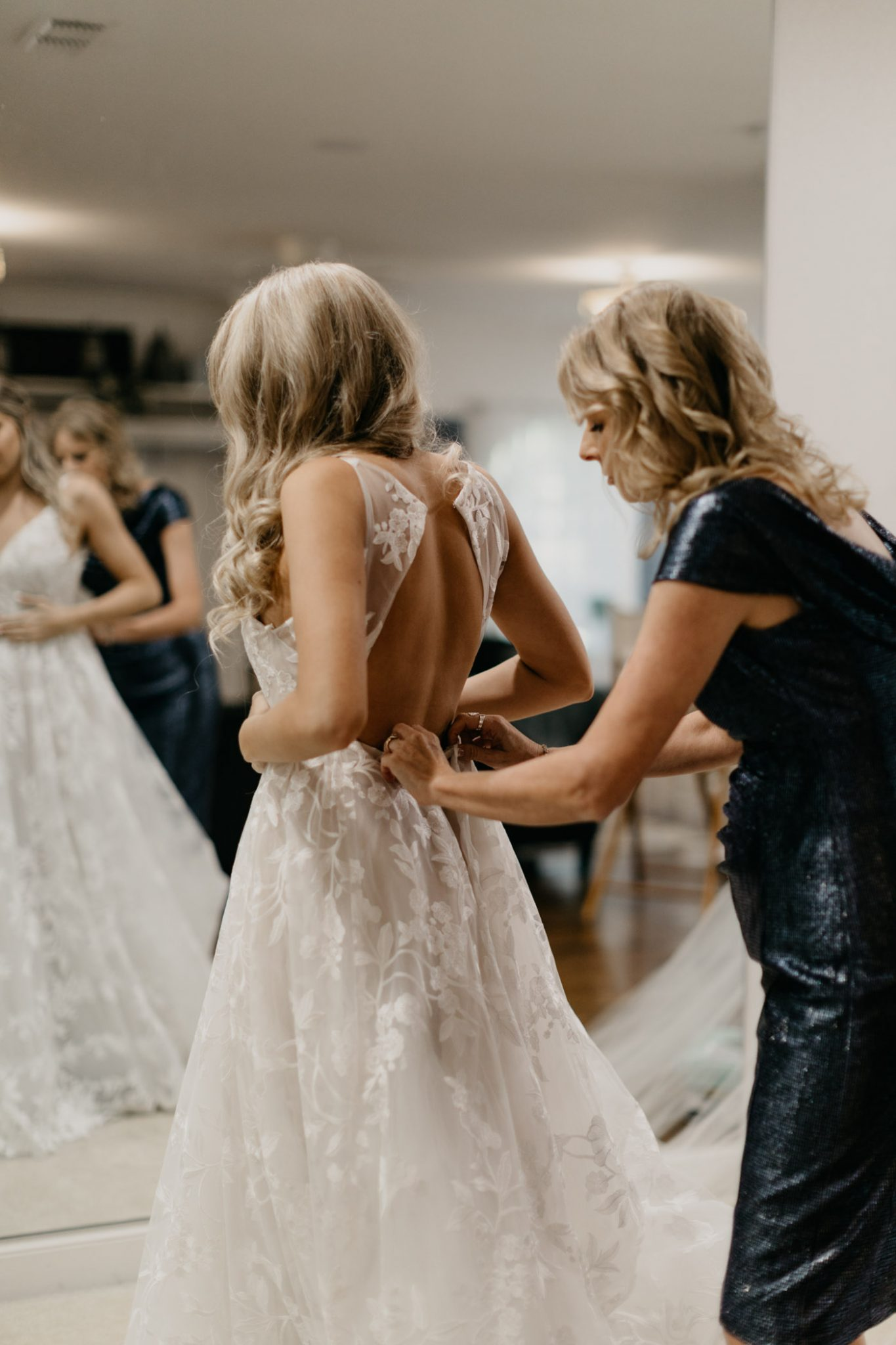 mom helping bride put on her wedding dress on her wedding day