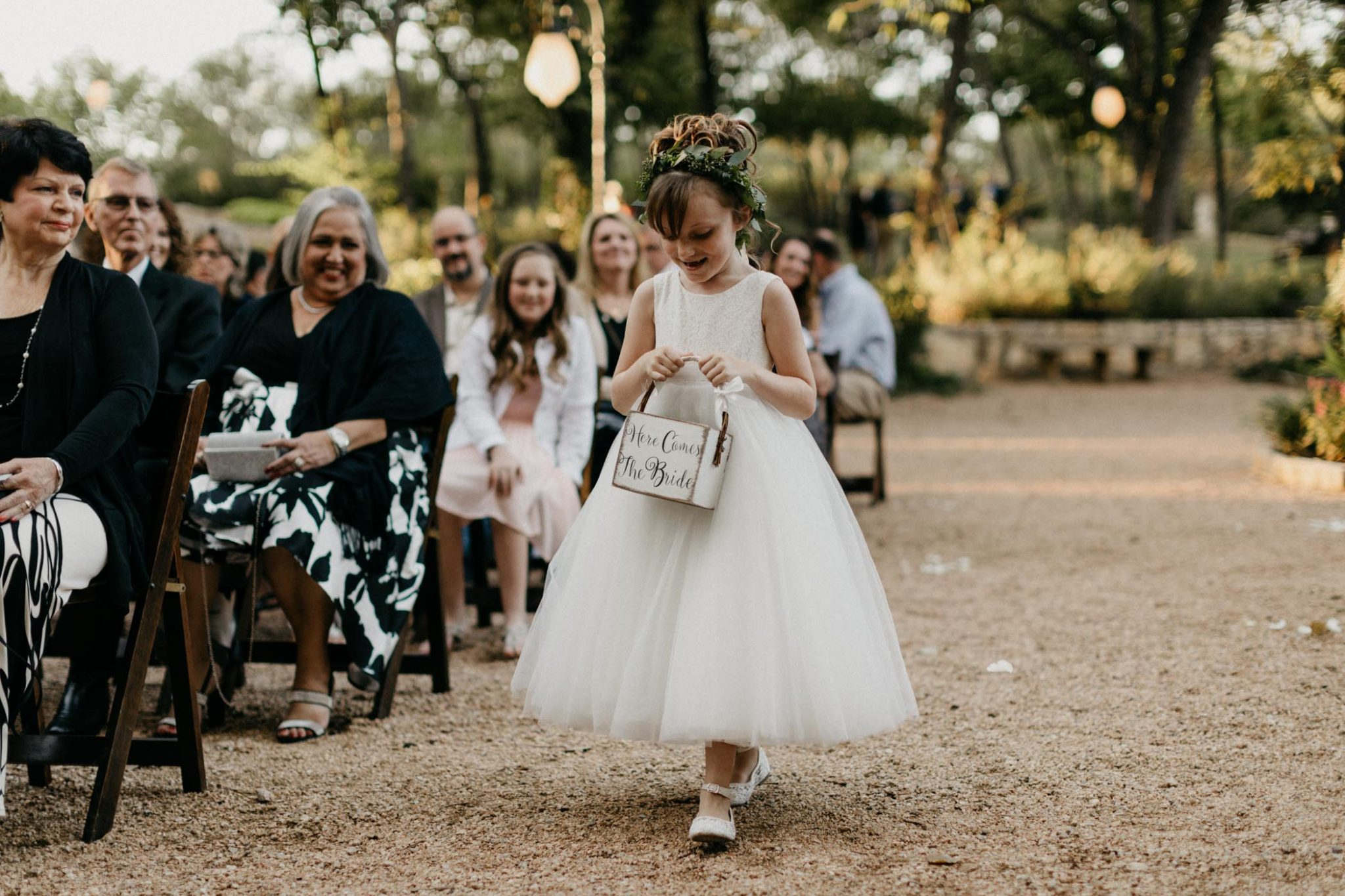 adorable flower girl walking down the aisle of an elegant outdoor wedding ceremony