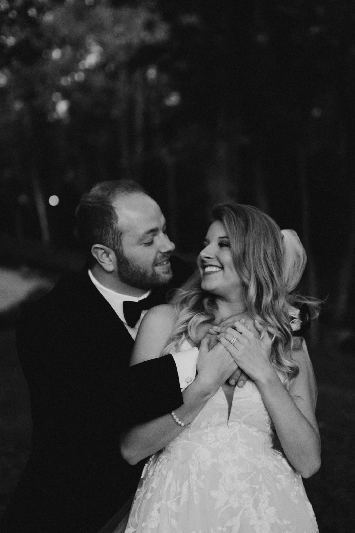 black and white photo of bride and groom being romantic after their outdoor wedding ceremony