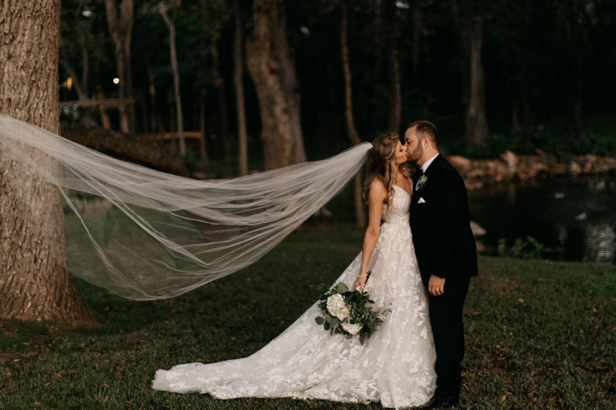 brides wedding veil blowing in the wind as she kisses her new husband