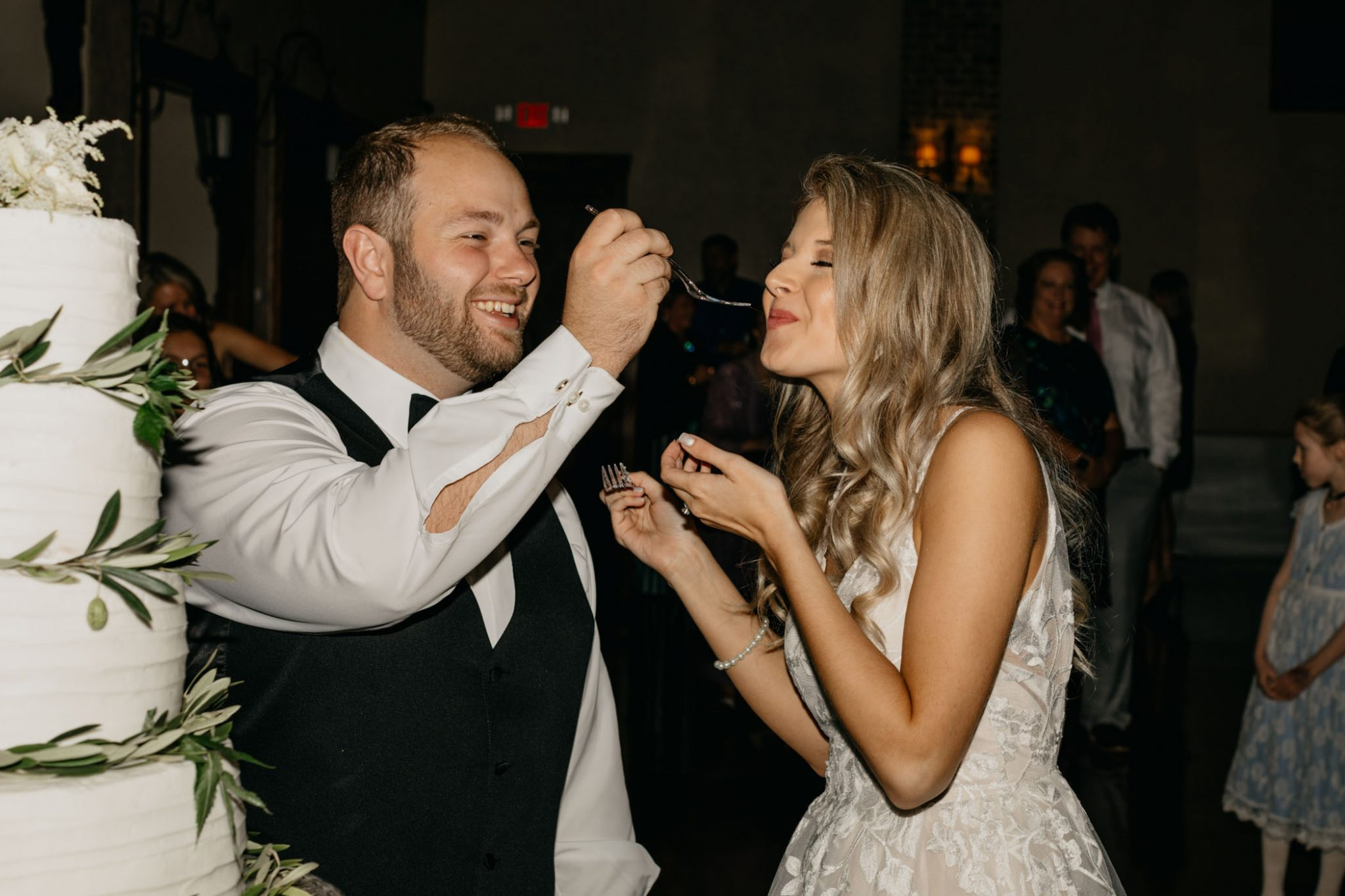 bride and groom feeding each other cake in Fort Worth photographer