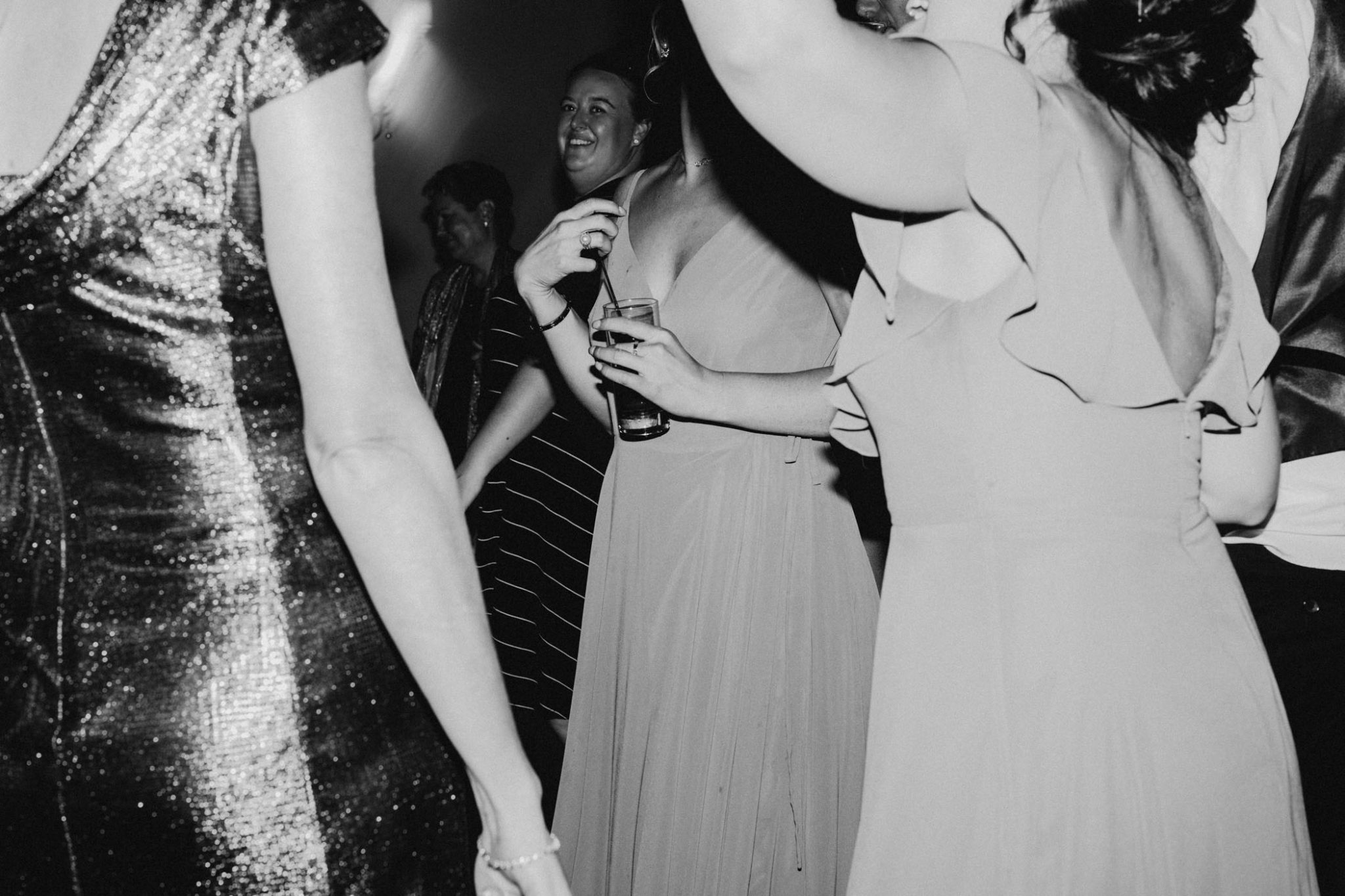 black and white photo of crazy wedding reception and bridal party having fun
