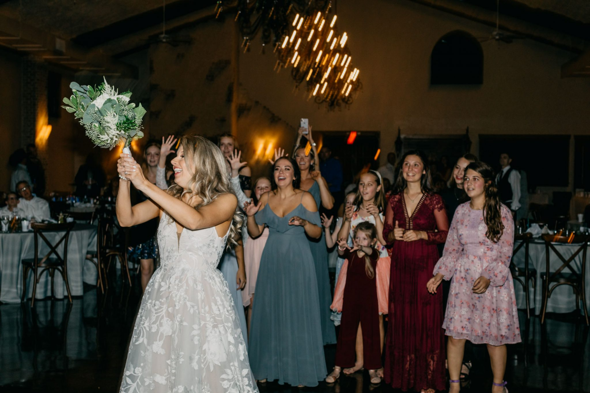 bride throwing bouquet after wedding ceremony