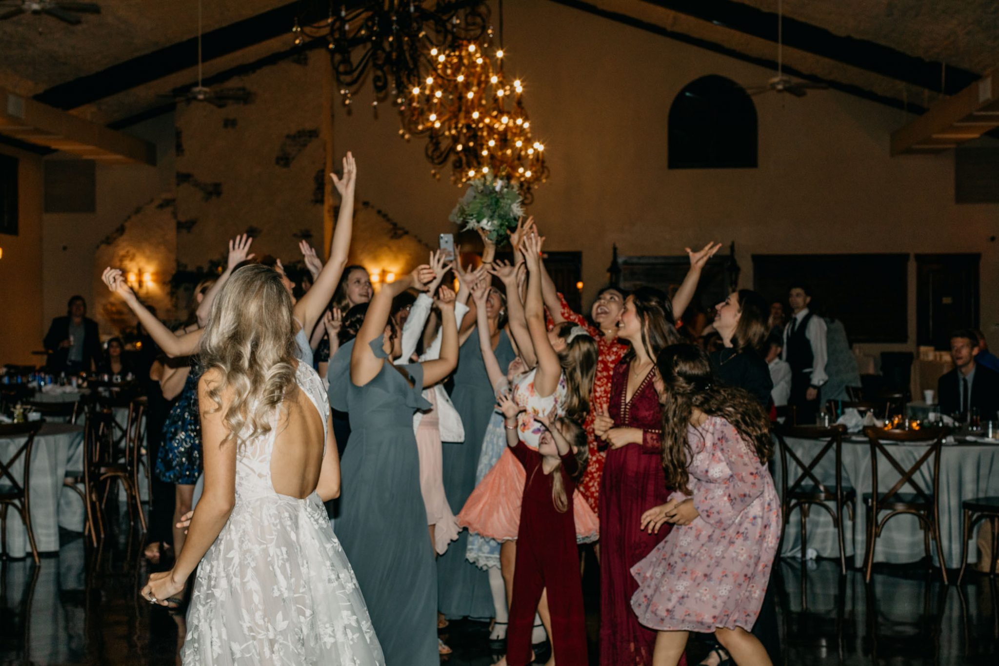 bridal party jumping for bouquet during outdoor wedding reception