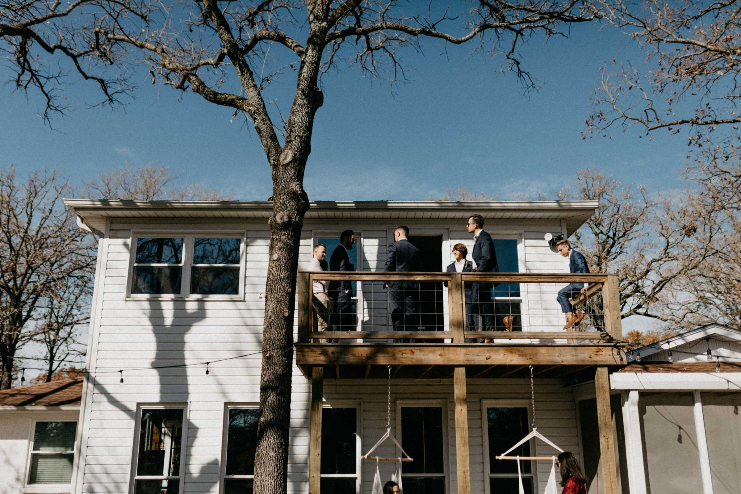 groomsmen hanging out on a balcony before the wedding day begins