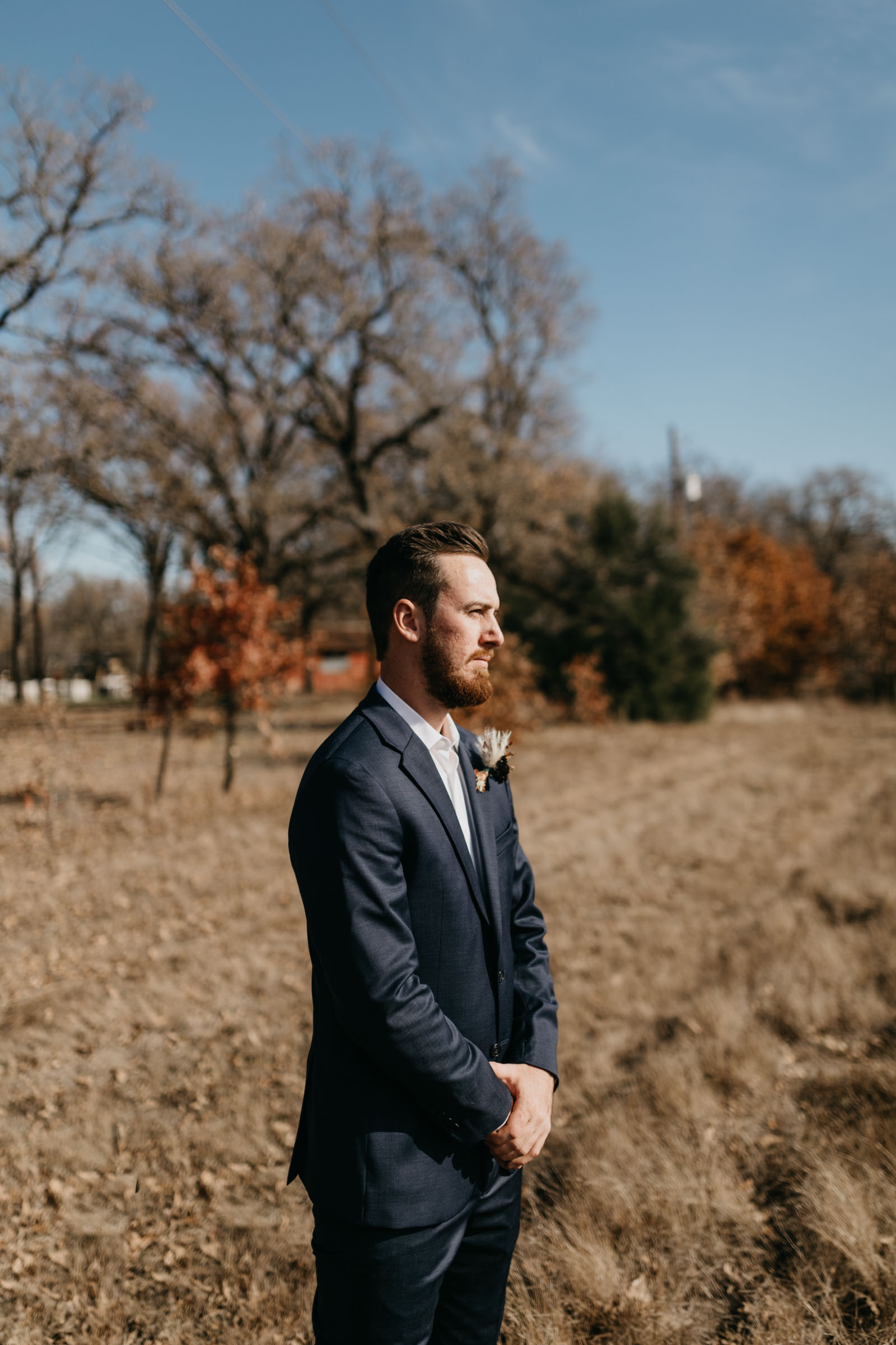 Groom waiting to see bride for the first time on their wedding day in a field