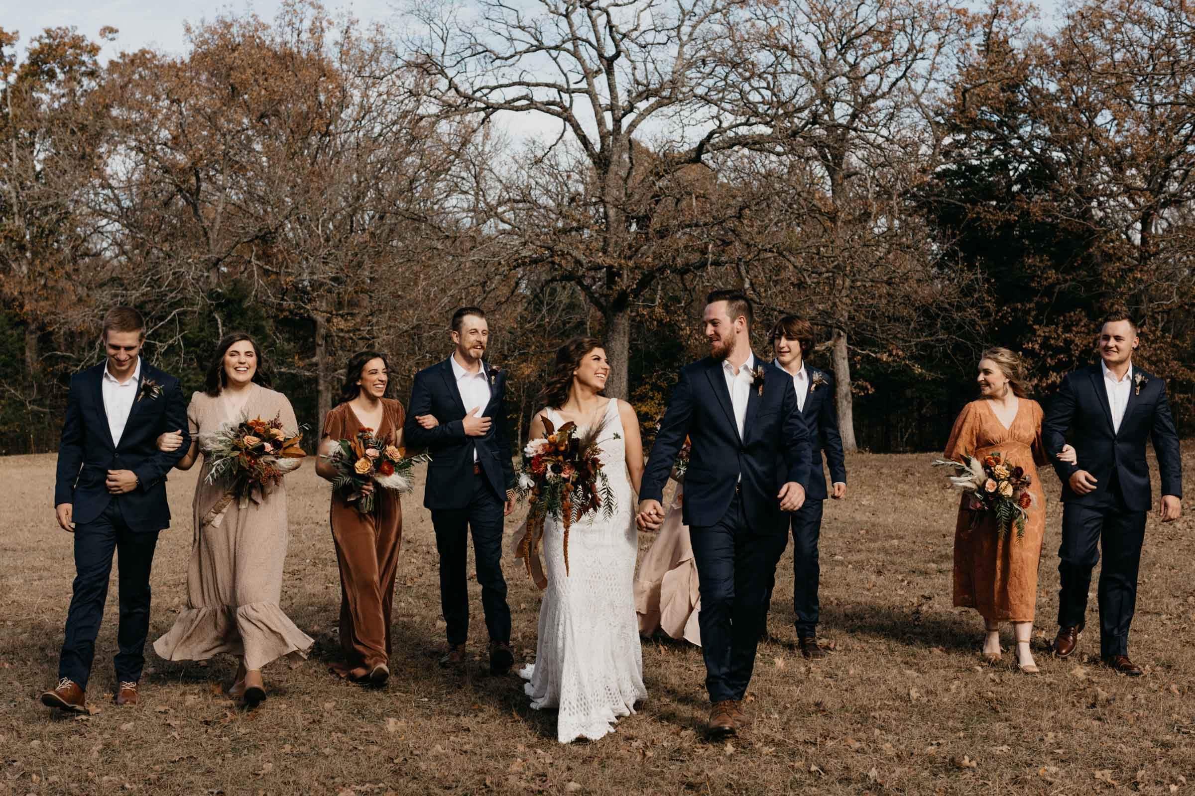 East texas bridal party holding their florals and walking behind bride and groom