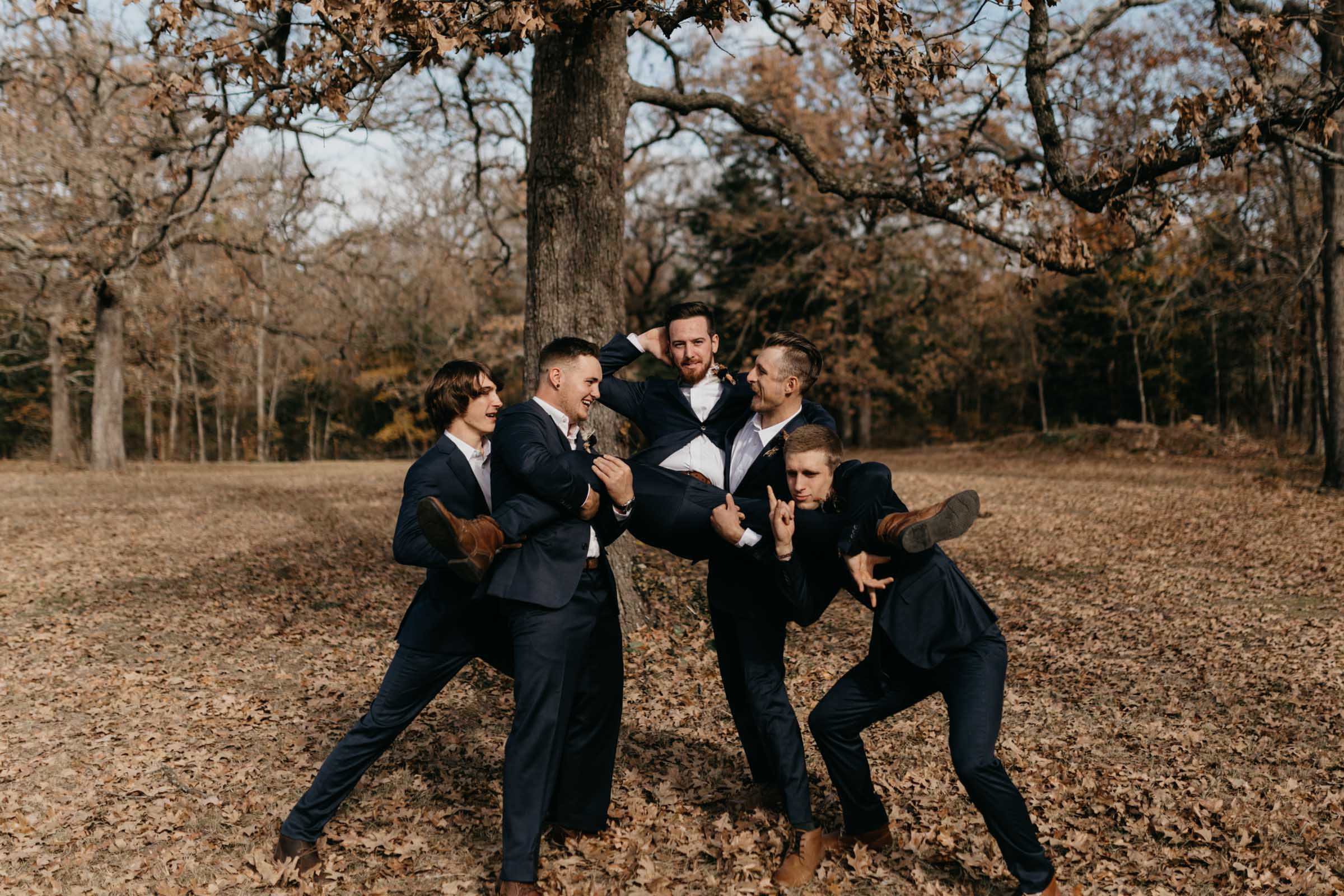 Groomsmen picking up the groom for a photo on their wedding day