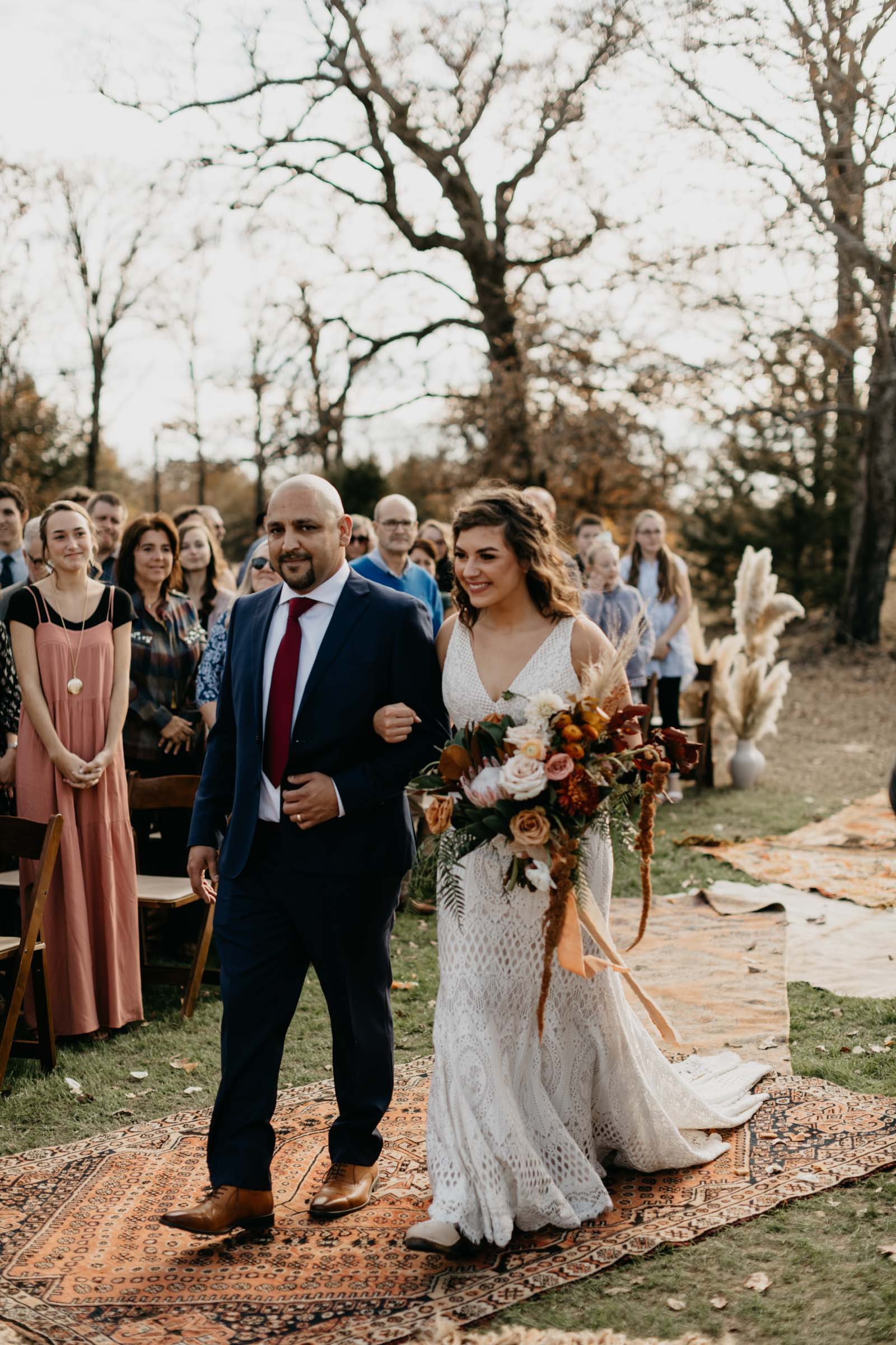 Brides father walking her down the aisle made of bohemian rugs