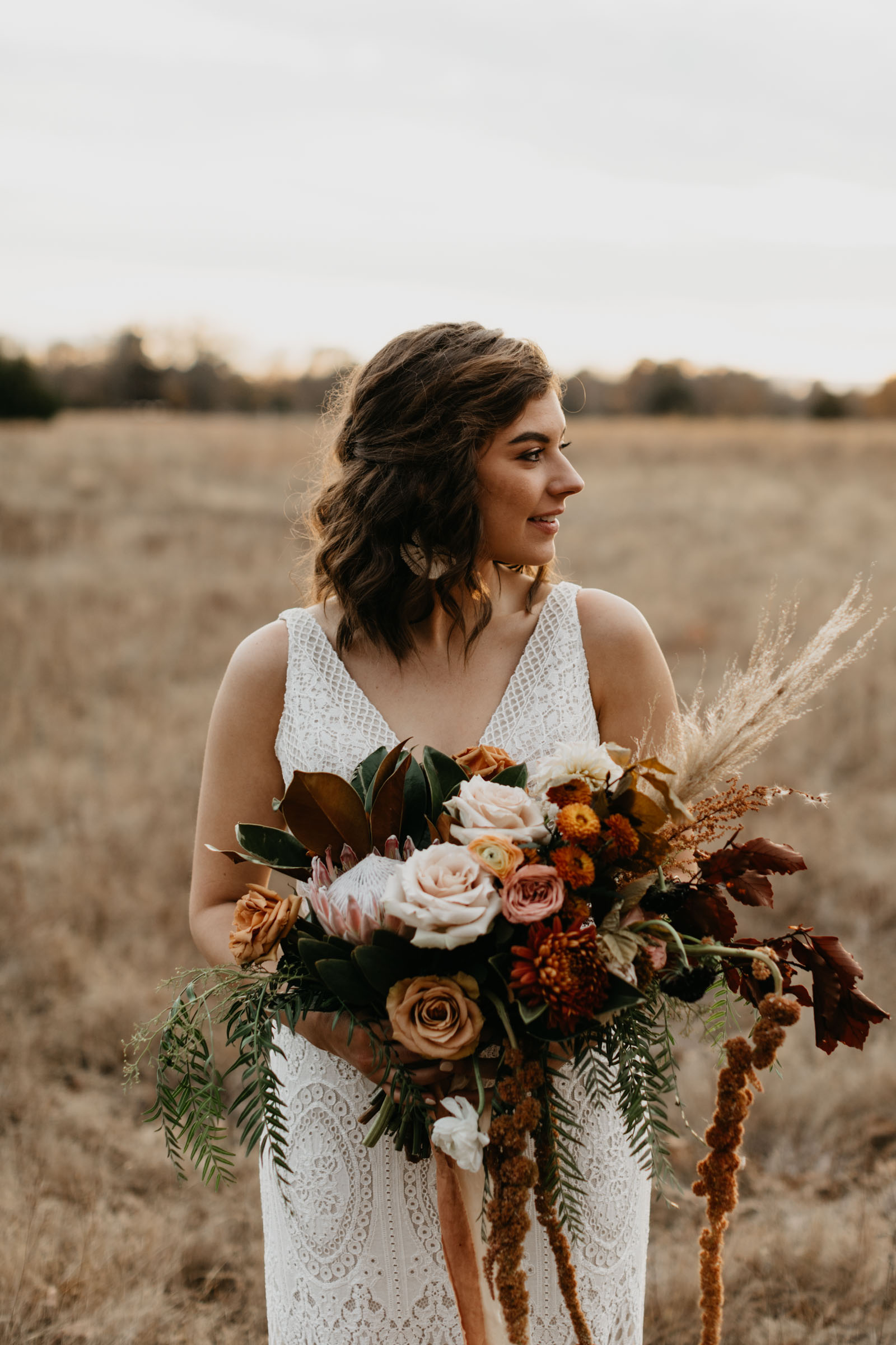 Beautiful bohemian bride holding large rust colored wedding bouquet for a bridal portrait