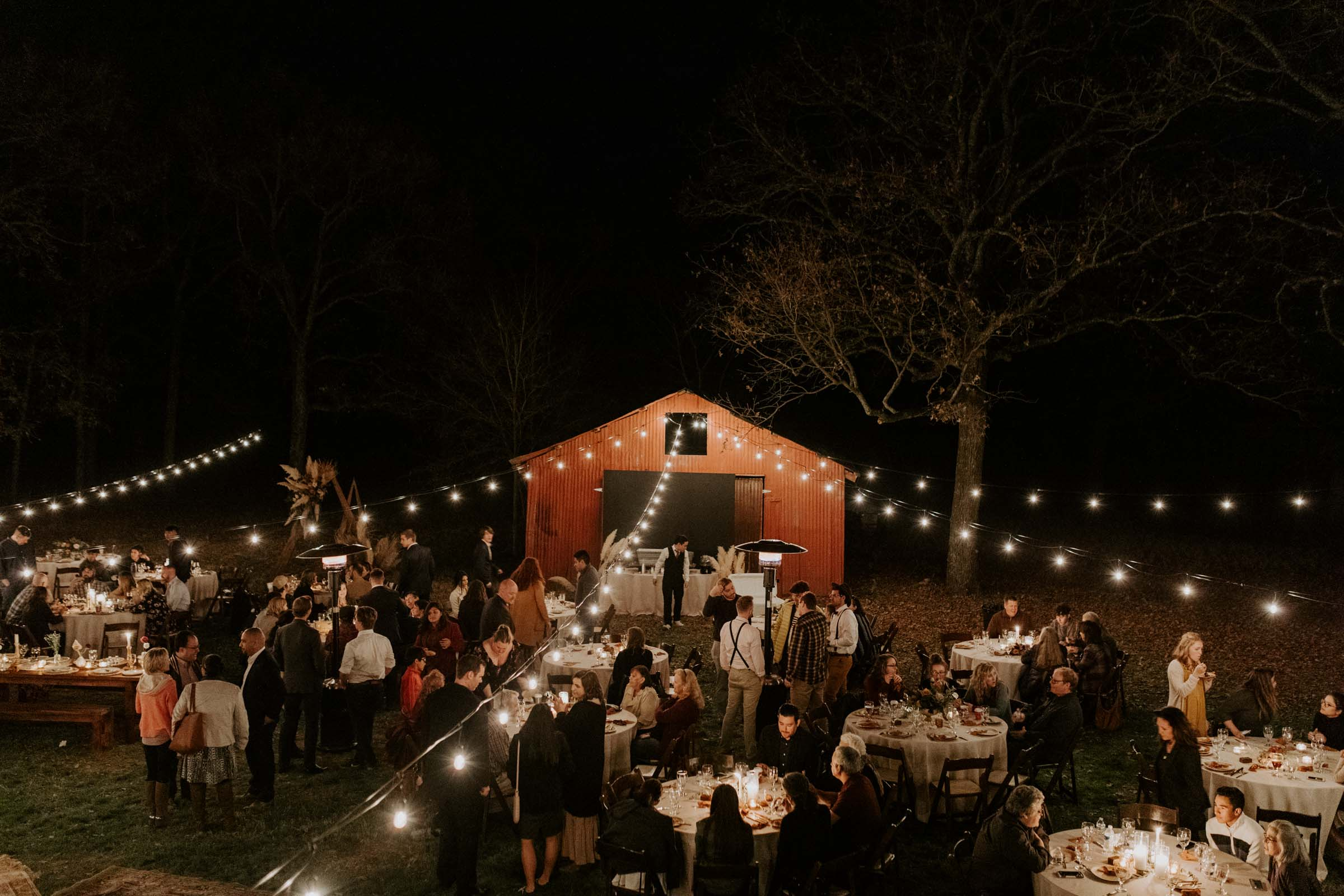 Backyard wedding string light decor with red barn central point