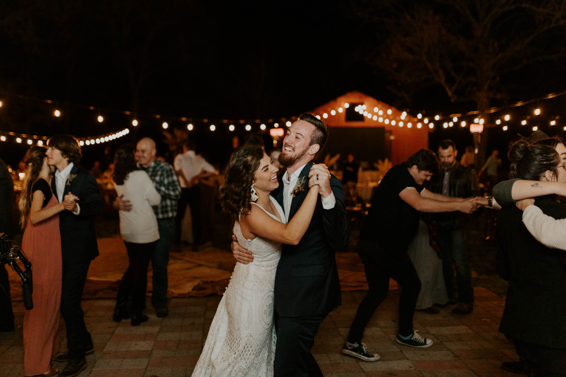 Bride and groom being goofy and dancing after dark on their wedding day